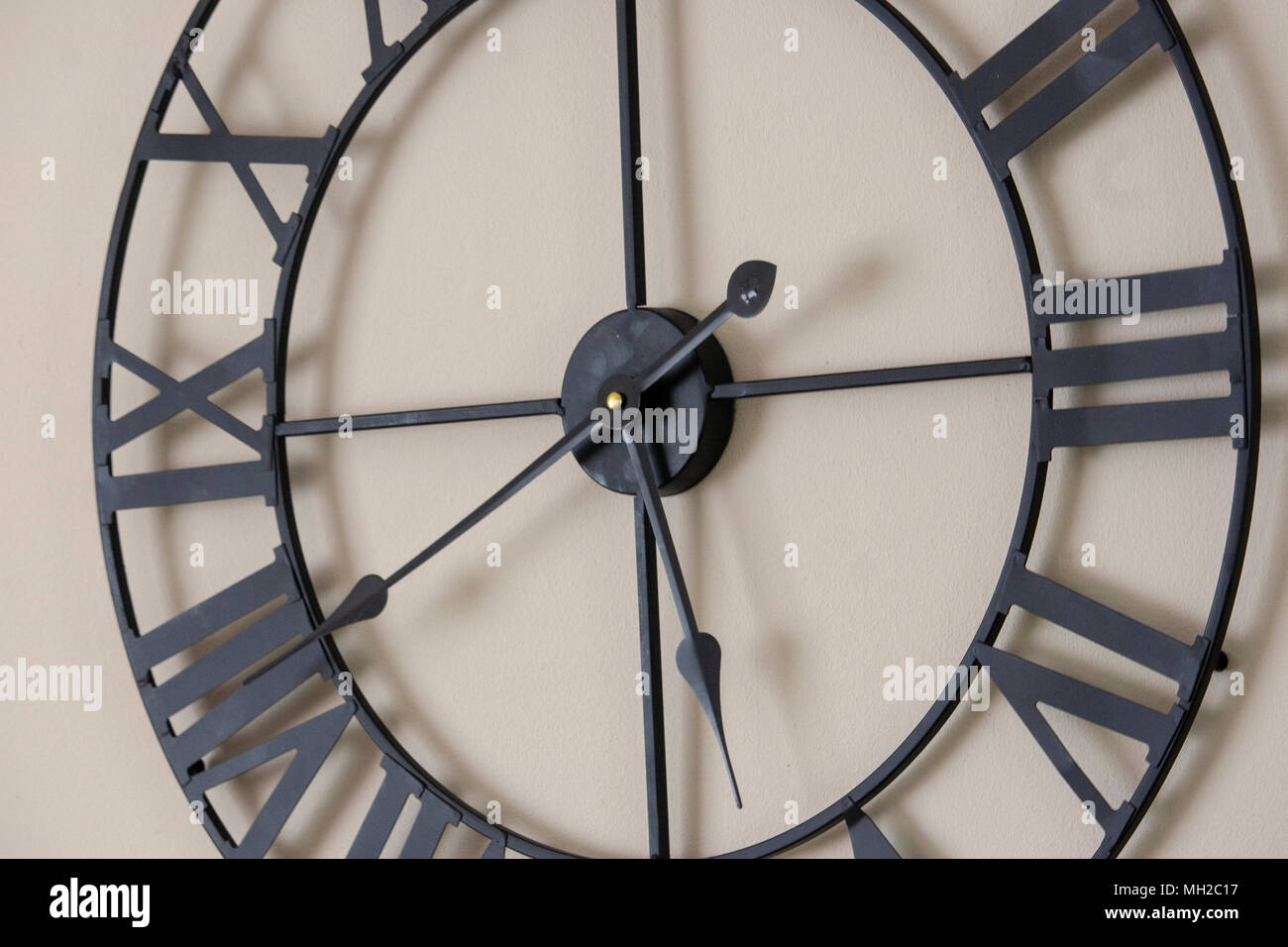 Black Clock Face with Roman Numerals and White Background - Stock Image