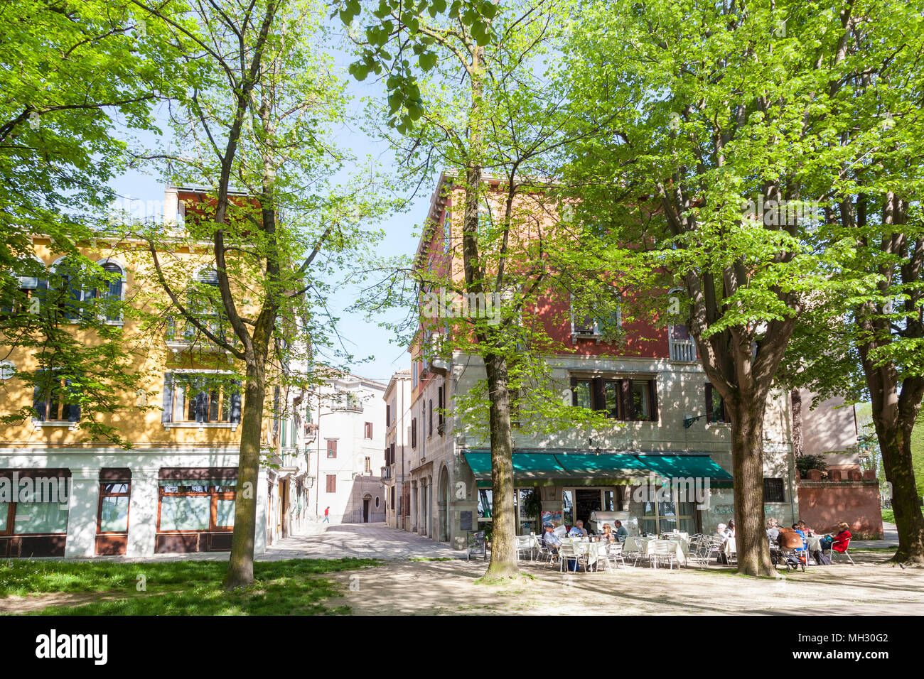Spring in Venice. Fresh green trees in the Parco della Rimembranze along Viale 1V Novembre, Sant'Elena, Venice, Veneto, Italy, Open air retsaurant Stock Photo