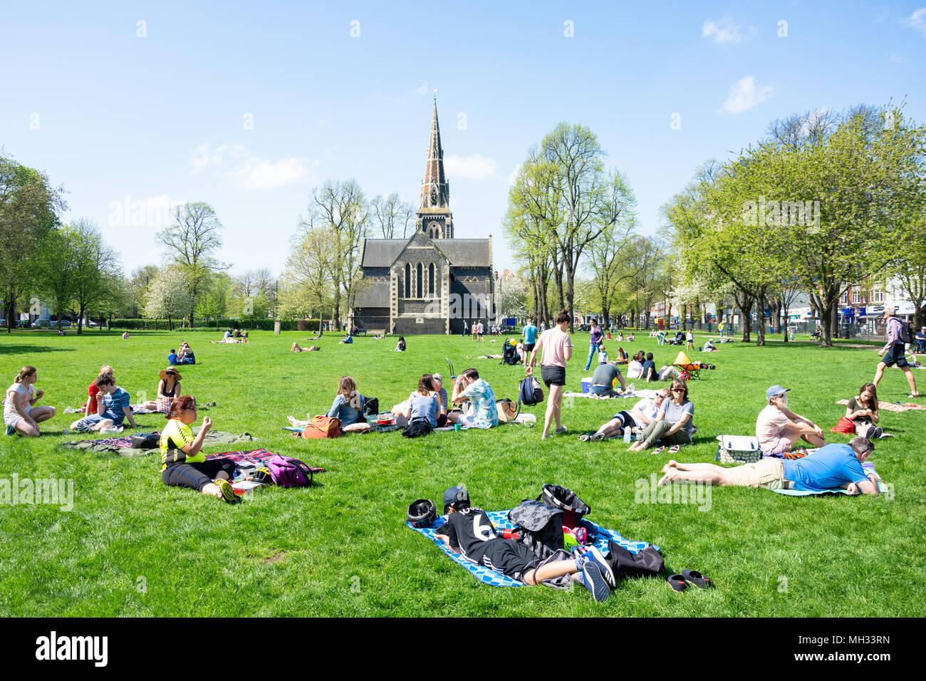 Turnham Green Church and sunbathers on grass, Turnham Green, Chiswick, London Borough of Hounslow, Greater London, England, United Kingdom - Stock Image