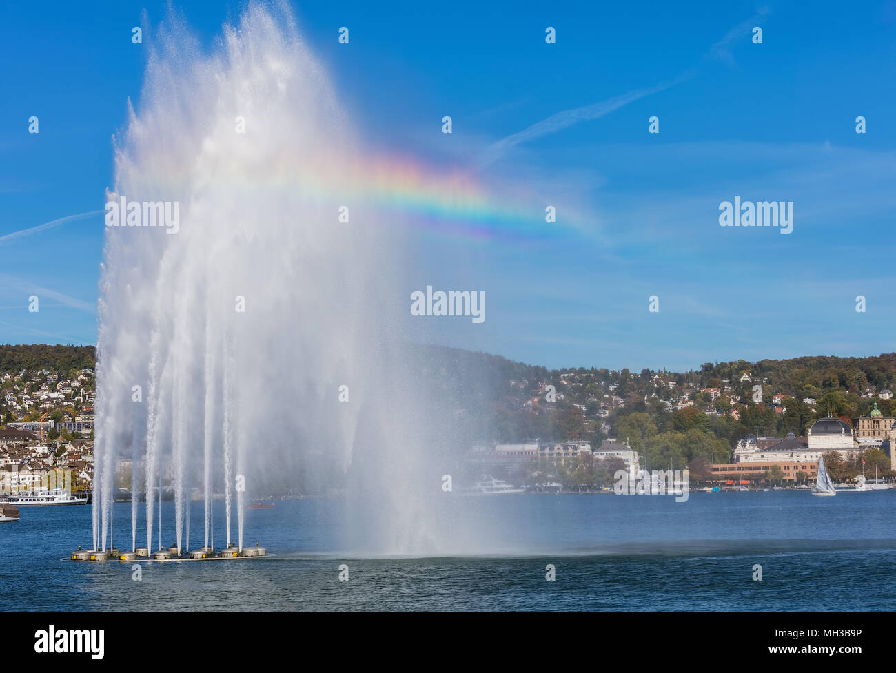 A fountain and boats on Lake Zurich in Switzerland, buildings of the city of Zurich in the background. The picture was taken at the beginning of Octob - Stock Image