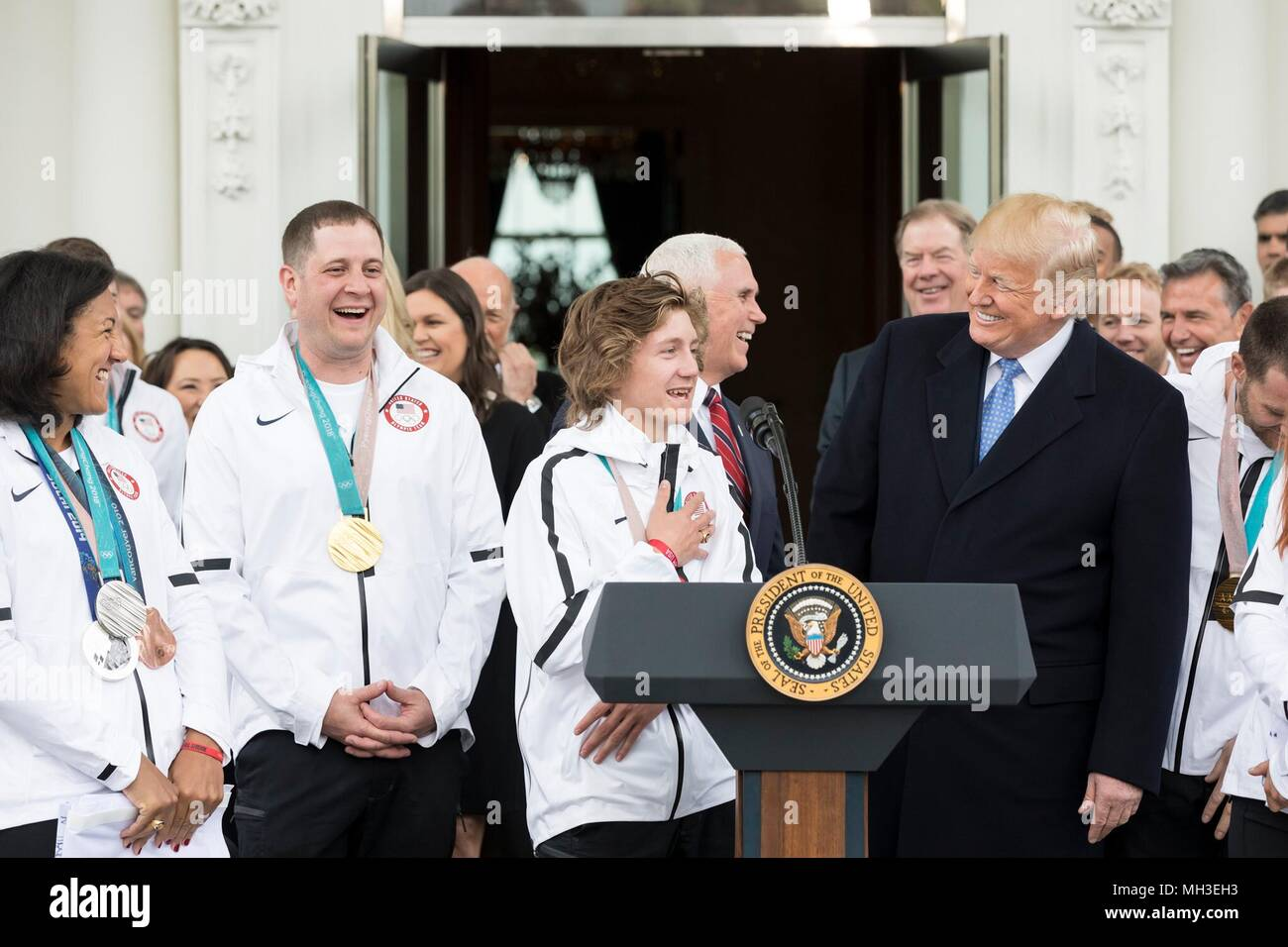 U.S. President Donald Trump shares a laugh with Olympic snowboarding gold medalist Redmond Gerard, center, during an event honoring Team USA Olympic and Paralympic athletes at the White House April 27, 2018 in Washington, DC. - Stock Image