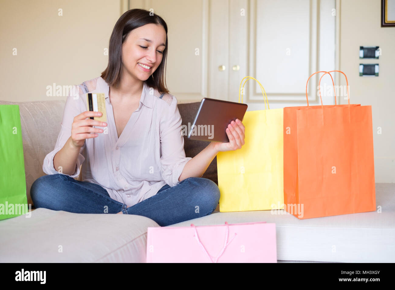 Happy young woman ordering and paying using credit card on online store - Stock Image