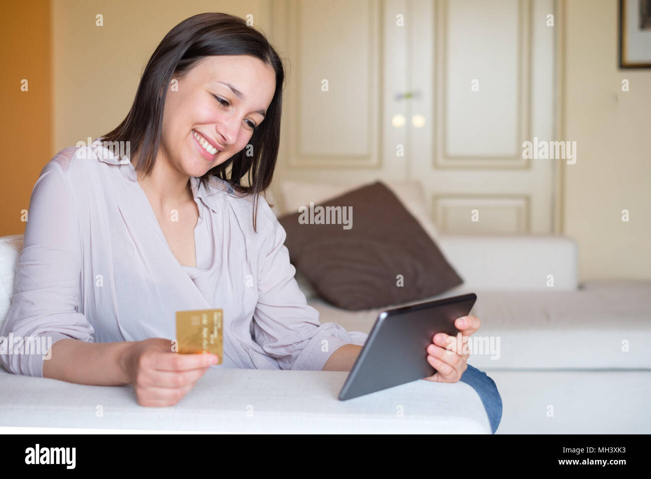 Young woman doing online shopping at home with safe bank credit card transaction - Stock Image