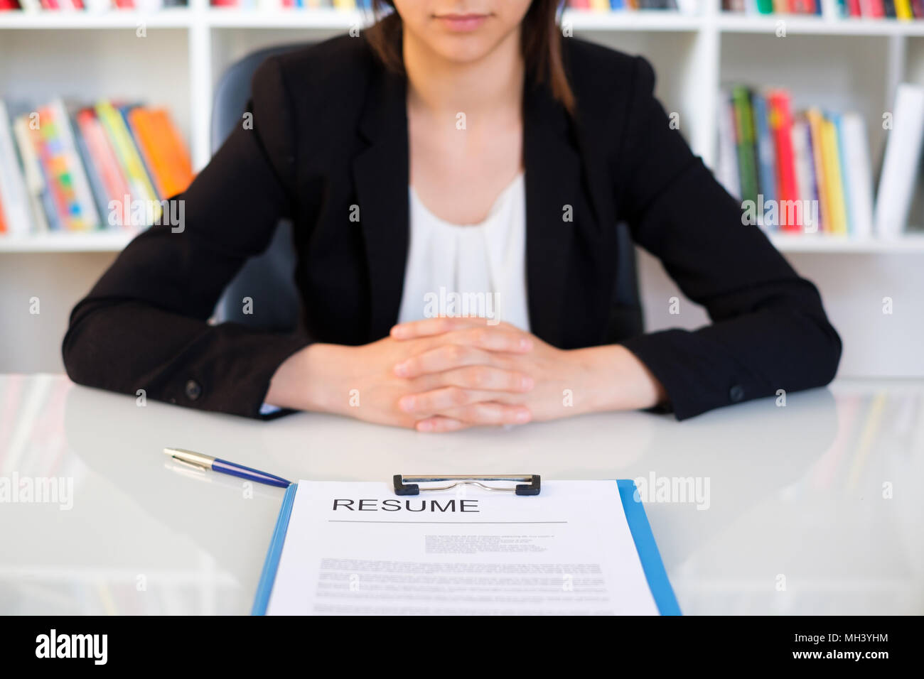 Young woman showing her cv resume and looking for a job - Stock Image