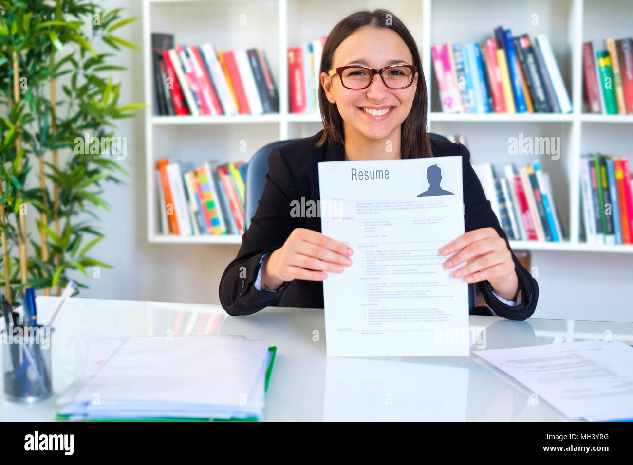 Woman searching job and showing her cv resume - Stock Image
