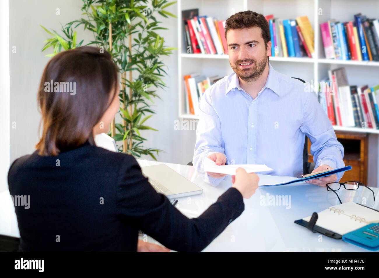 Young candidate showing his curriculum cv during successful job interview - Stock Image