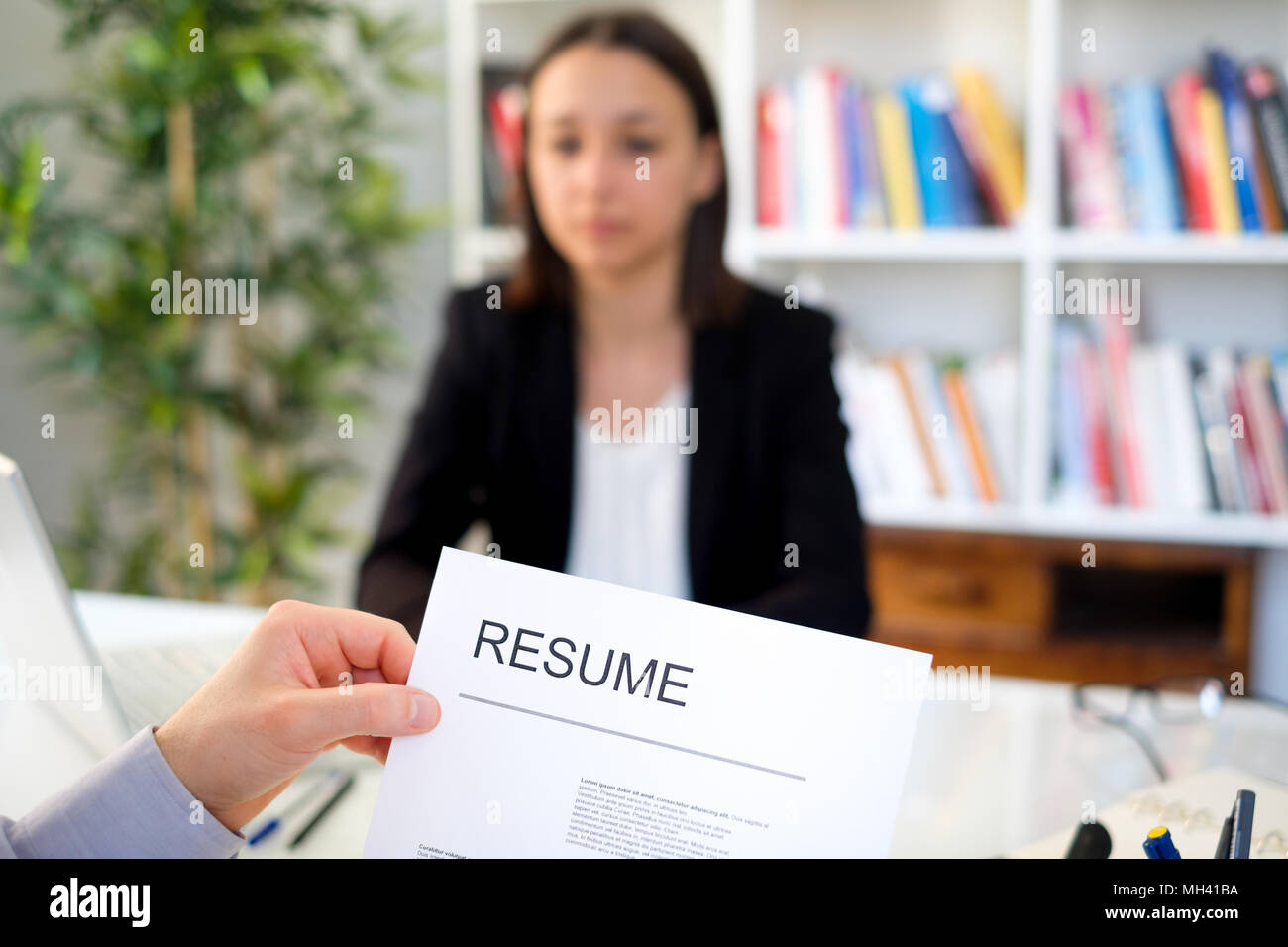 Young woman during job interview , main focus on the cv resume - Stock Image
