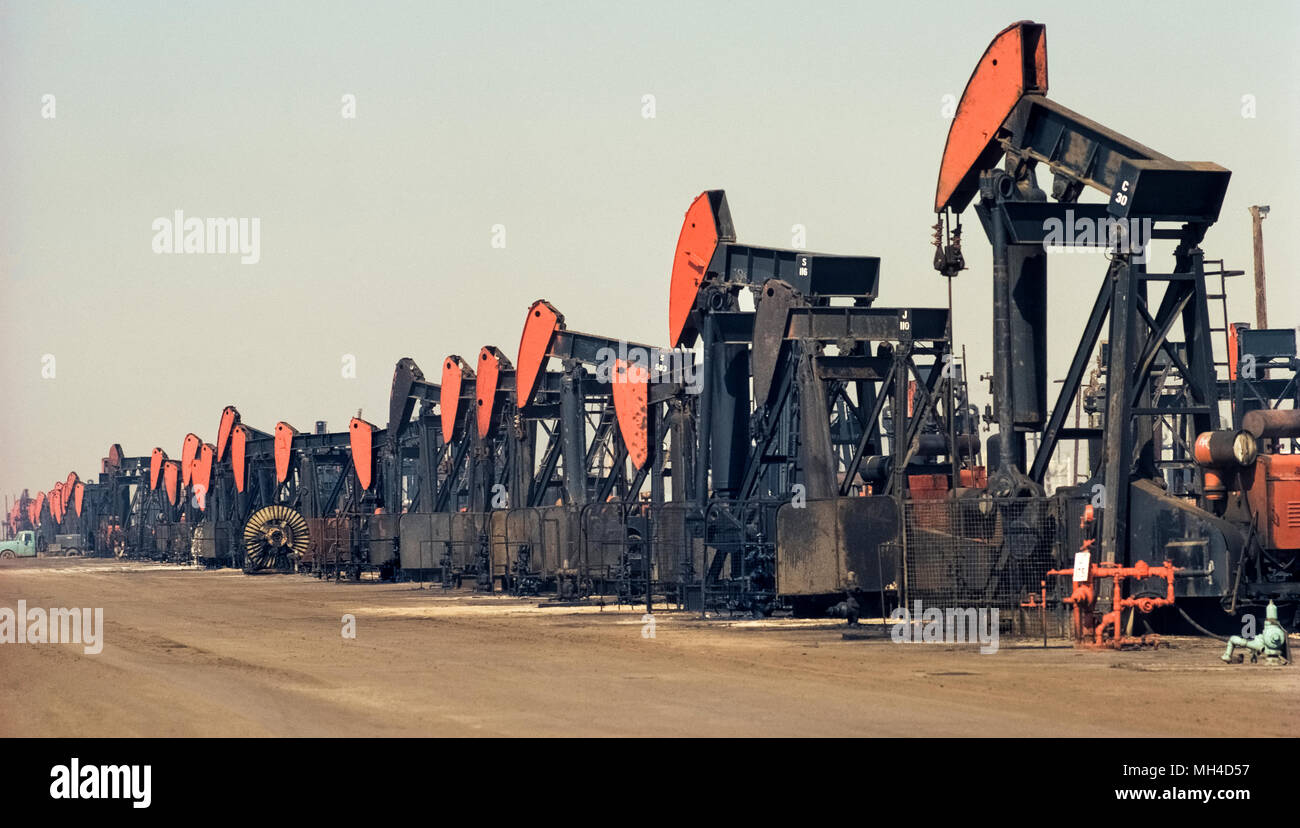 A long line of mechanical pumps busily extracting petroleum from underground is seen on a hazy day in Huntington Beach, California, USA, where 'black gold' was first struck in 1920 and began an oil boom in Southern California. Officially named pumpjacks but also known as nodding donkeys, these vintage oil rigs were photographed in 1972. In recent years, many of the pumps and oil-drilling derricks in this coastal city have been replaced by housing developments. Historical photograph. - Stock Image