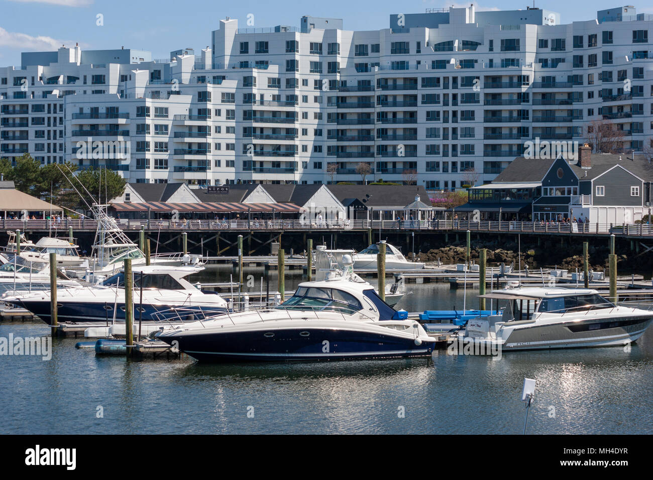 Yachts moored at Marina Bay docks, in front of a waterfront boardwalk, restaurants and condominium complex, in Quincy, Massachusetts, USA. Stock Photo