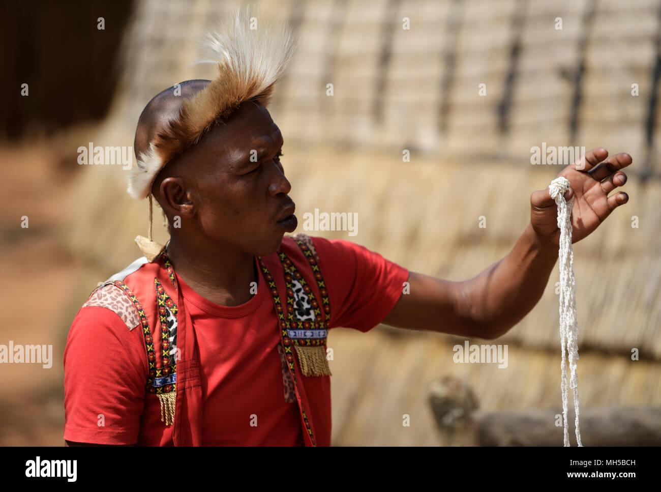 Eshowe, KwaZulu-Natal, South Africa, single young man in traditional Zulu dress explaining cultural customs of beadwork at Shakaland theme village Stock Photo