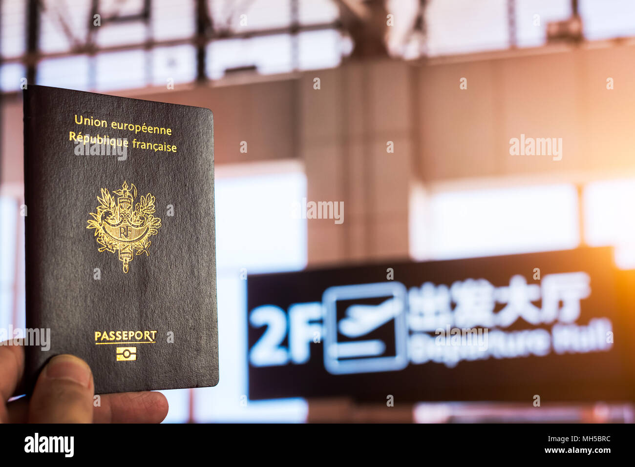 Hand holding a french passport in a chinese airport departure hall with the sun passing through the windows - Stock Image
