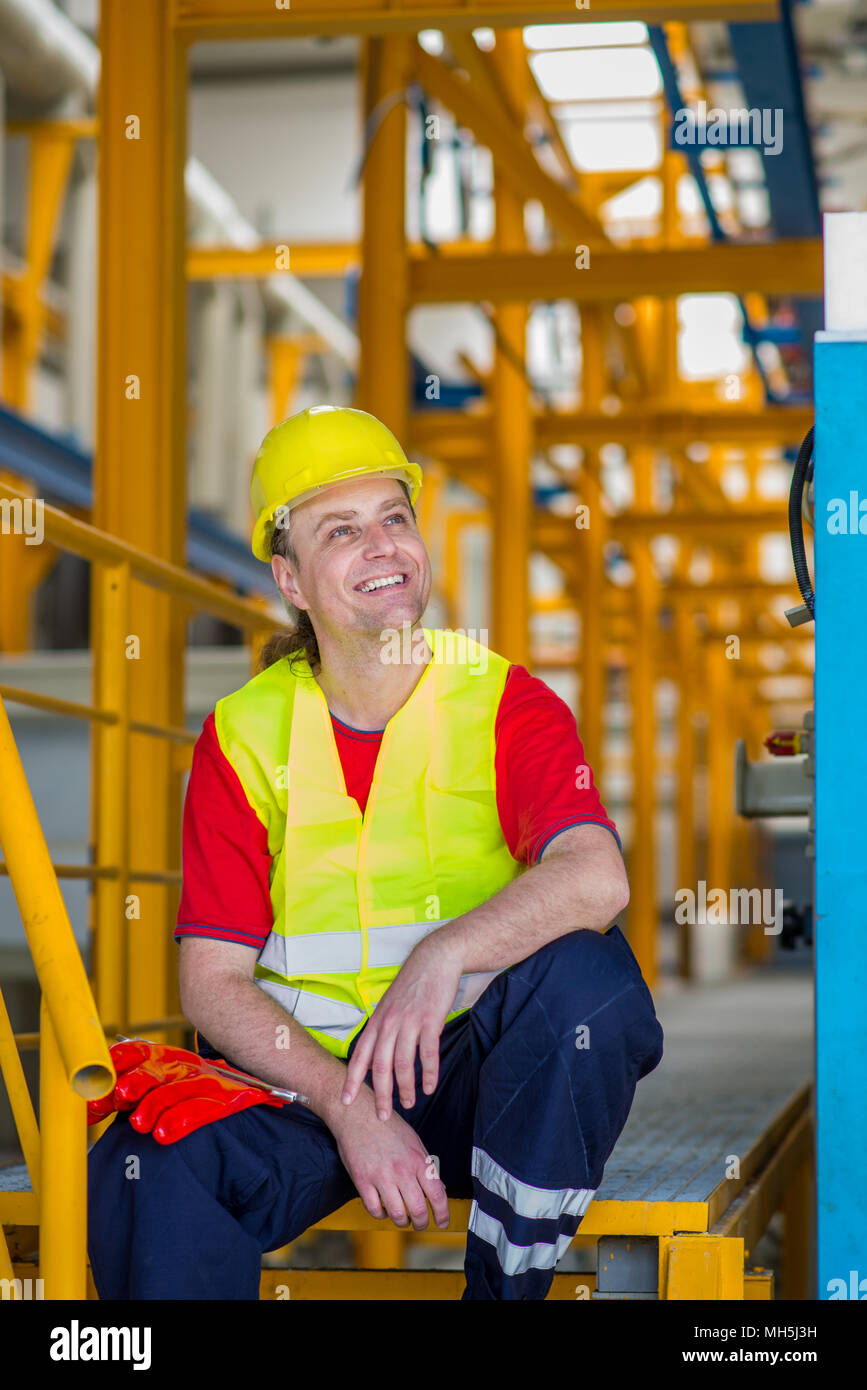 Happy worker in yellow reflective suit with yellow helmet sitting in a factory and smiling - Stock Image