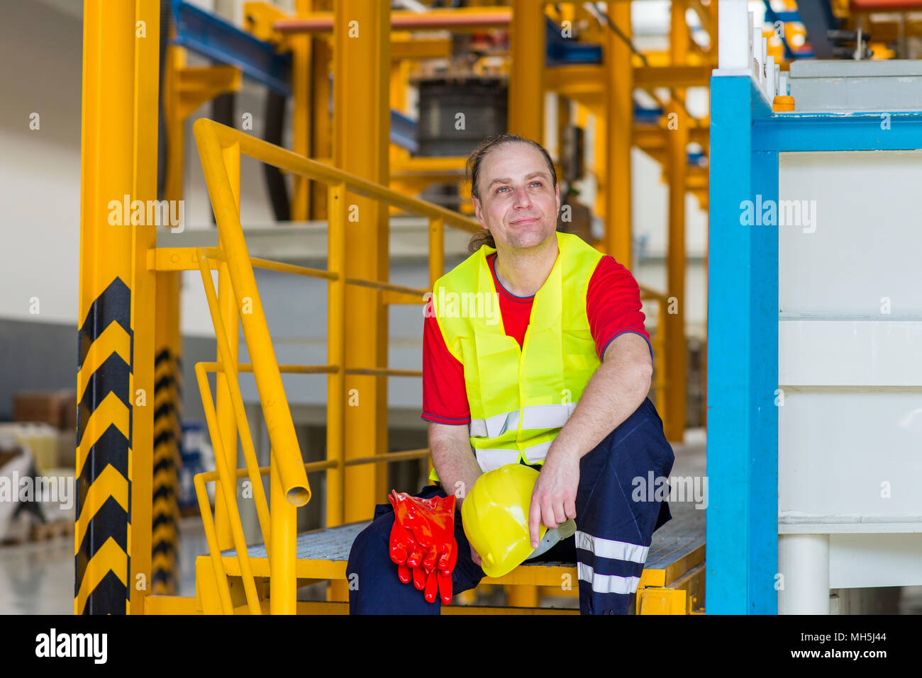 Worker in a factory sitting and resting during a work - Stock Image