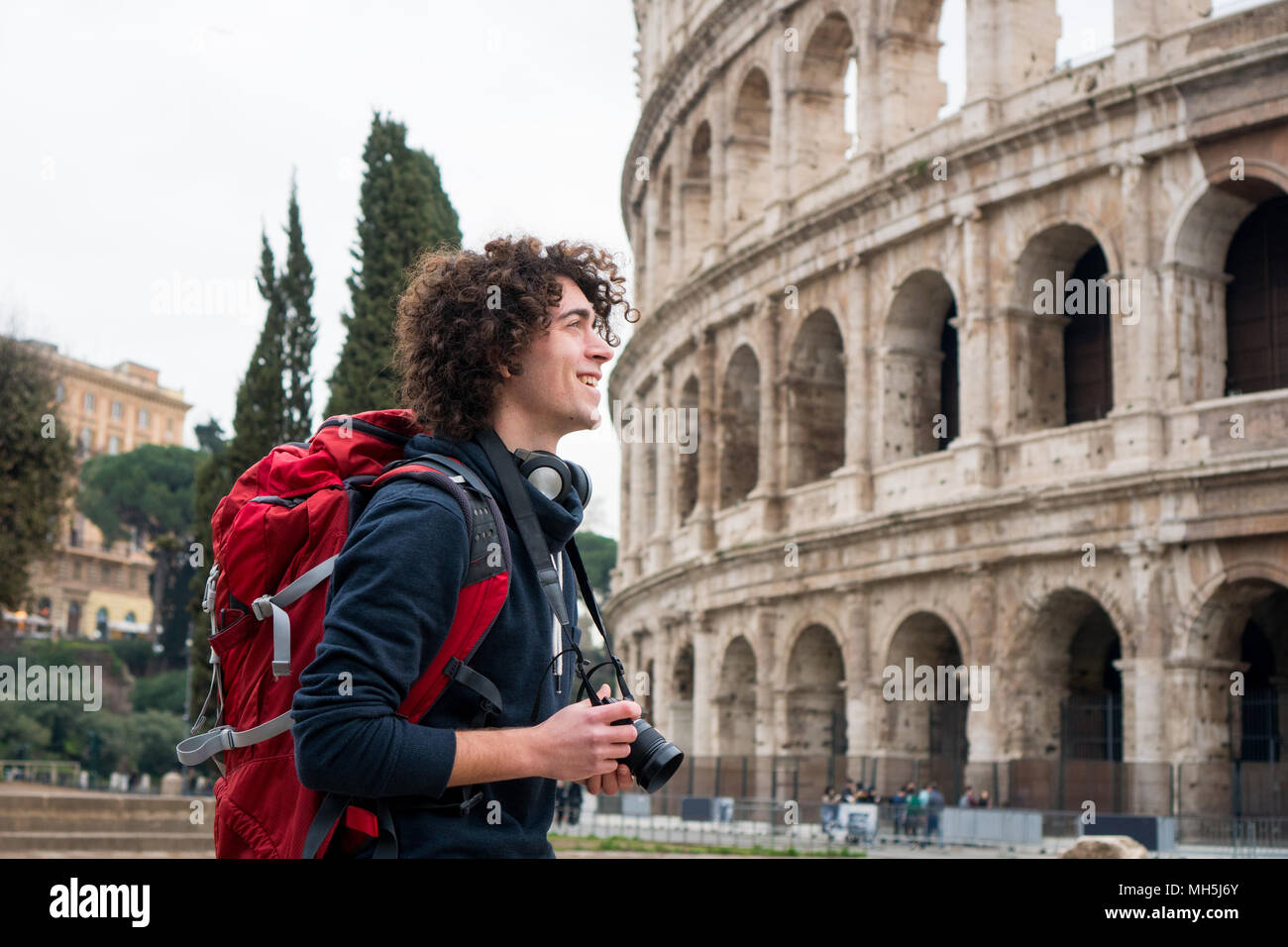 Handsome young tourist man with curly hair with a camera and backpack taking pictures of Colosseum in Rome, Italy. Young tourist taking pictures of Co - Stock Image