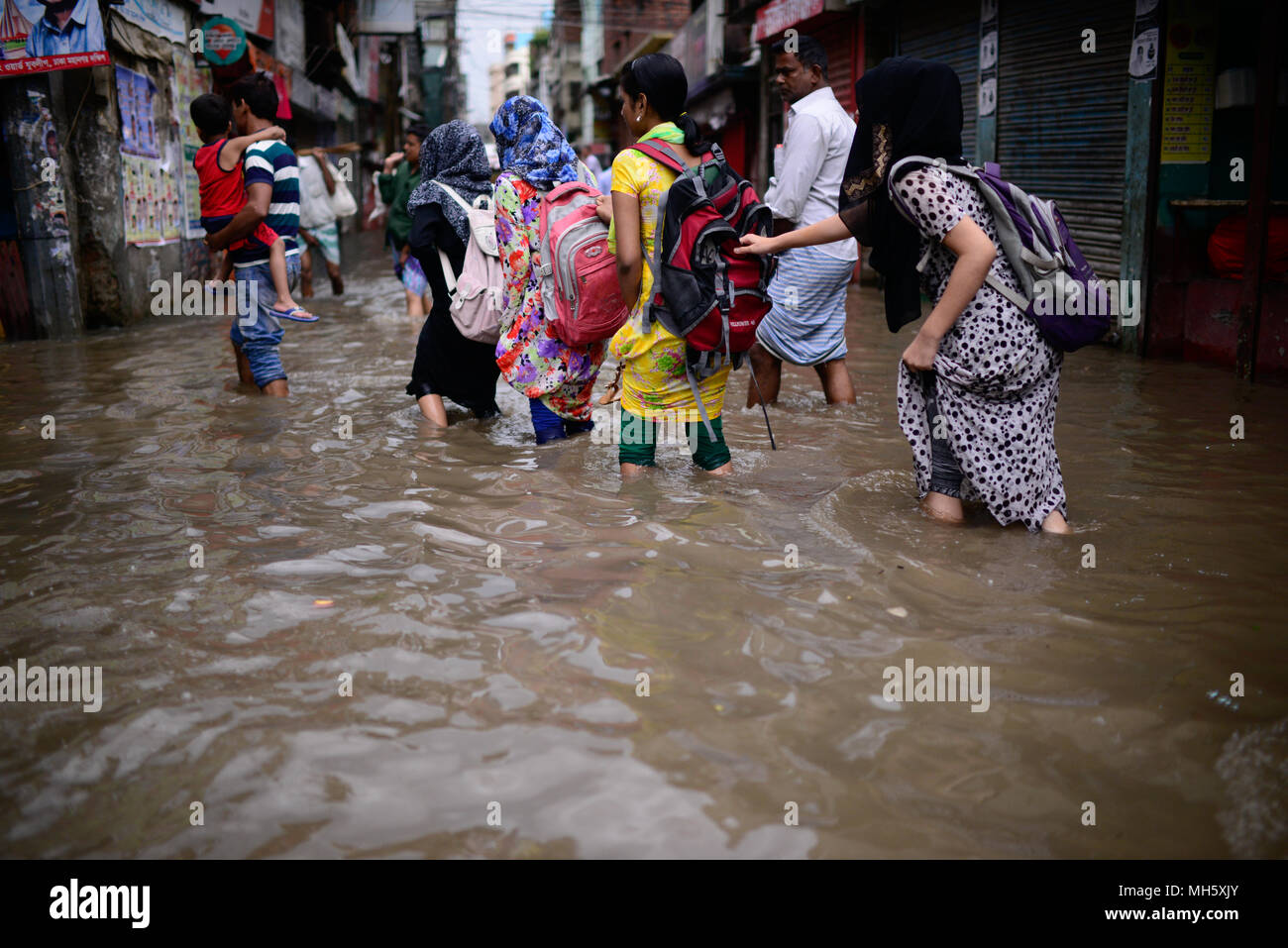 Dhaka, Bangladesh. April 30, 2018. Dhaka city dwellers ride rickshaw through the flooded road after the heavy rainfall in Dhaka, Bangladesh on April 30, 2018. Al least 14 people have killed during the lightning and thunderstorms, disrupting life in the capital city where heavy rain flooded many roads according to reports.  Credit: Rakib Hasan/Alamy Live News - Stock Image