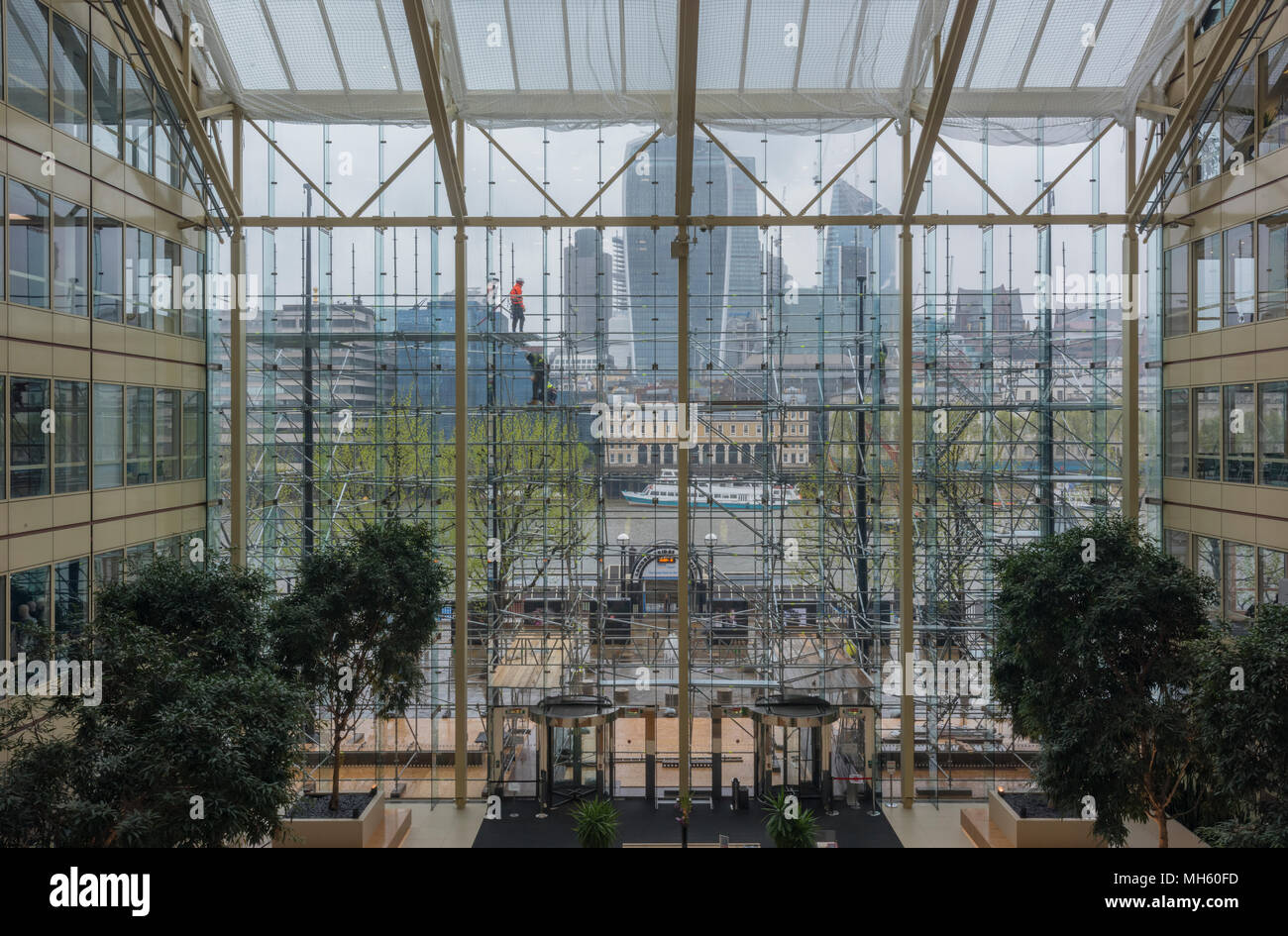 London, UK. 30th April, 2018. Brave scaffolders battling with the high winds and late April rain and cold at the Cottons centre on the South bank of the river Thames in central London. Scaffolders clipped onto the building to protect against falling from height on a large scaffold in central London. Credit: Steve Hawkins Photography/Alamy Live News - Stock Image