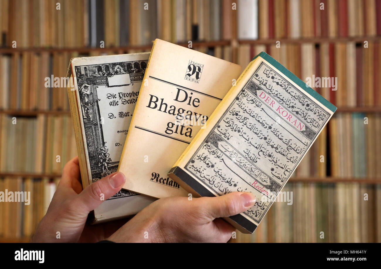 19 April 2018, Rostock, Germany: Bookseller Frank Weisleder shows from the Reclam series a three-part Bible (l-r), the 'Bhagavad gita', a kind of Indian Bible, and the Koran, in the background is the book wall with his complete collection of 1380 volumes of the 'Reclam Universalbibliothek', which were published in the GDR between 1963 and 1990 in the Leipzig Reclam publishing house. He has been collecting for over 20 years. (to 'Rostock: complete private collection of Reclamheften from GDR time' from 01.05.2018) Photo: Bernd Wüstneck/dpa - Stock Image