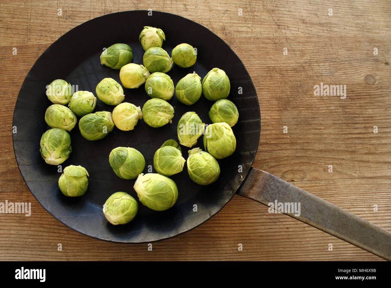 composition of fresh brussels sprouts in an iron pan on a wooden board - Stock Image