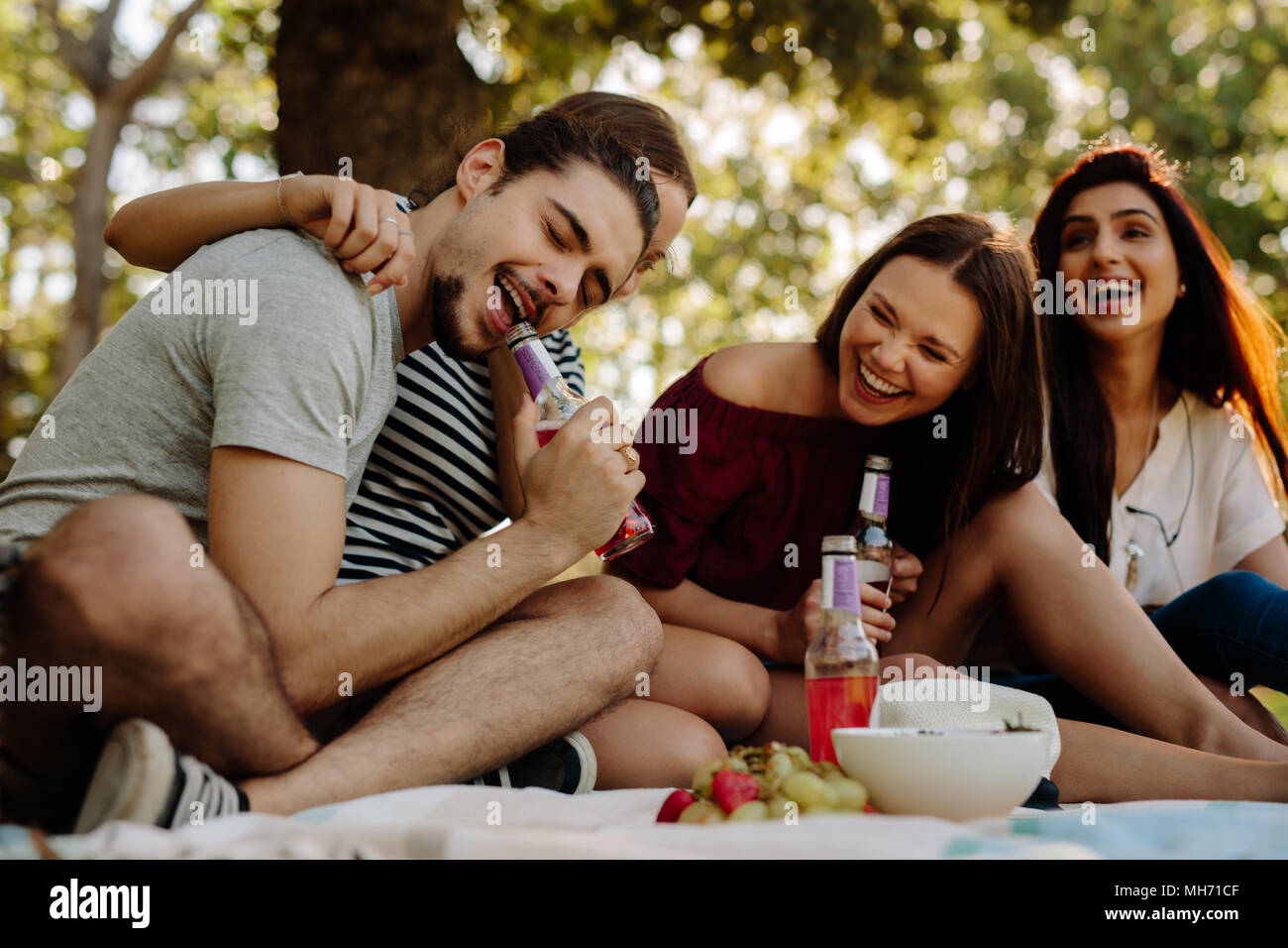 Man opening a bottle with his teeth and women sitting by smiling. Group of friends enjoying with drinks at picnic. - Stock Image