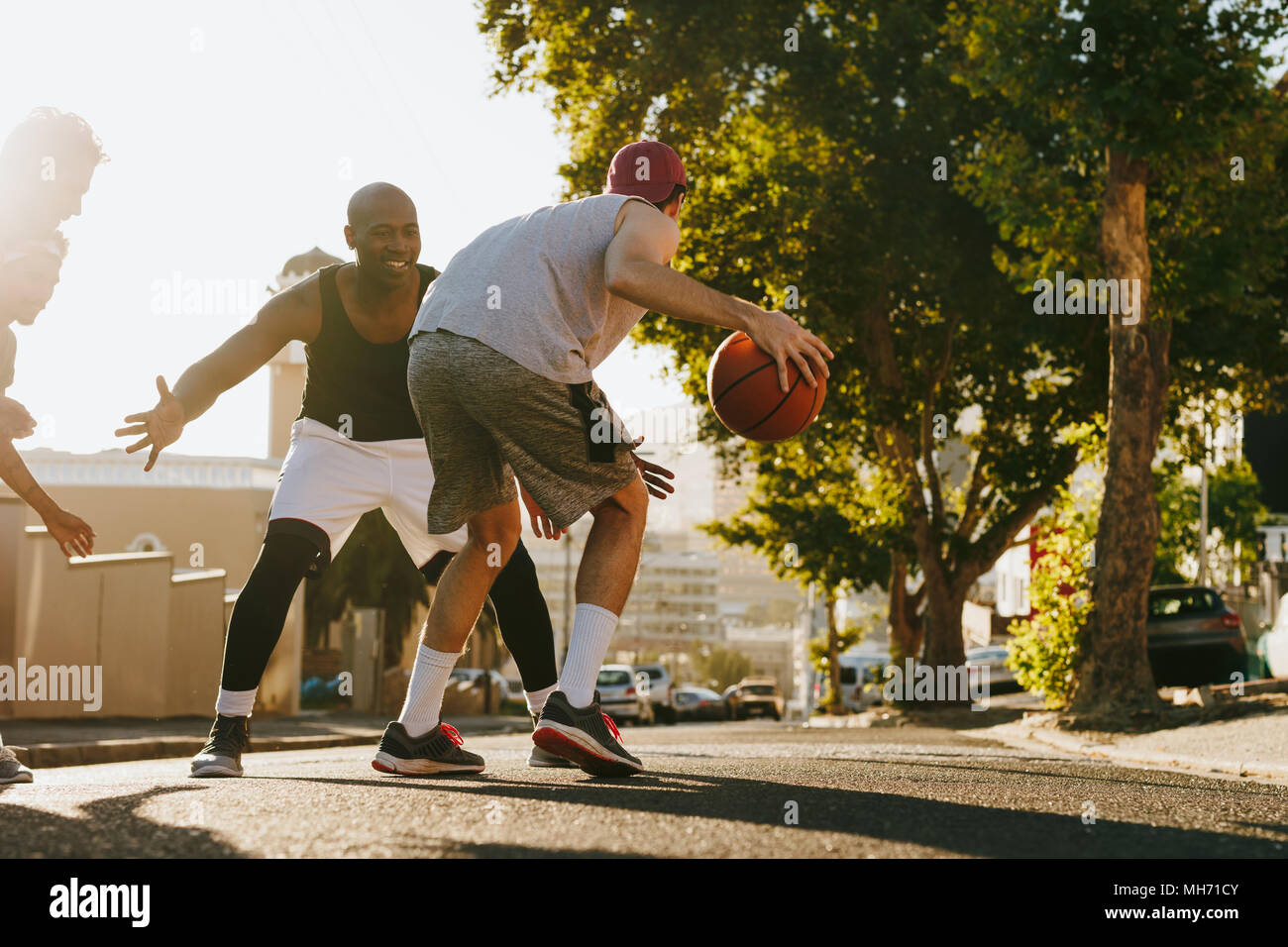 Men playing basketball game on a sunny day on an empty street. Four men playing basketball on street. Stock Photo