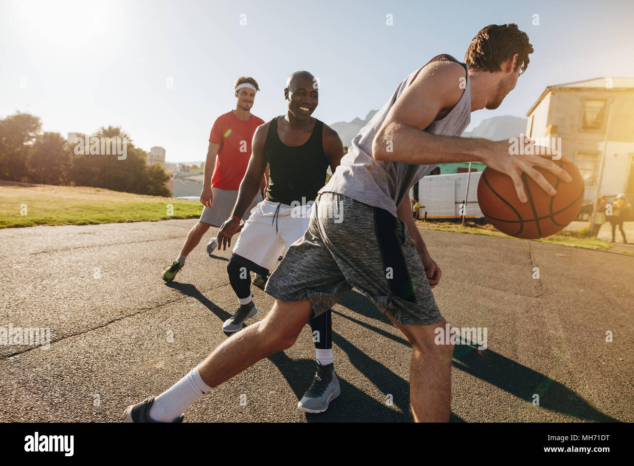 Men playing basketball game on a sunny day. Men practicing basketball skills in play area. Stock Photo