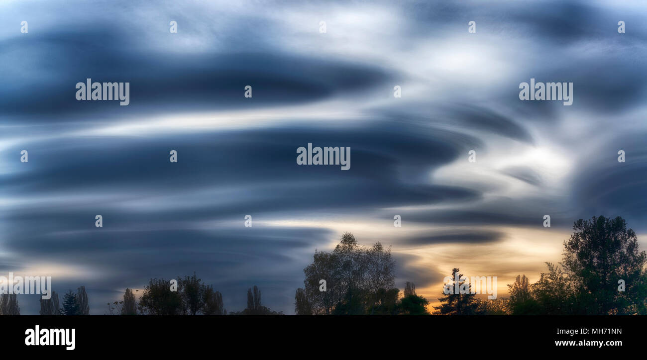 Incredible lenticular clouds in the sky during a sunset in the autumn season - Stock Image