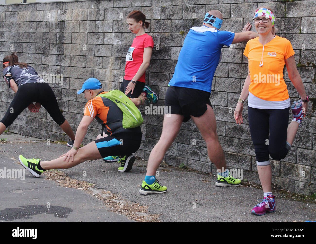 Runners doing stretching before the start of a marathon - active fit people - Stock Image