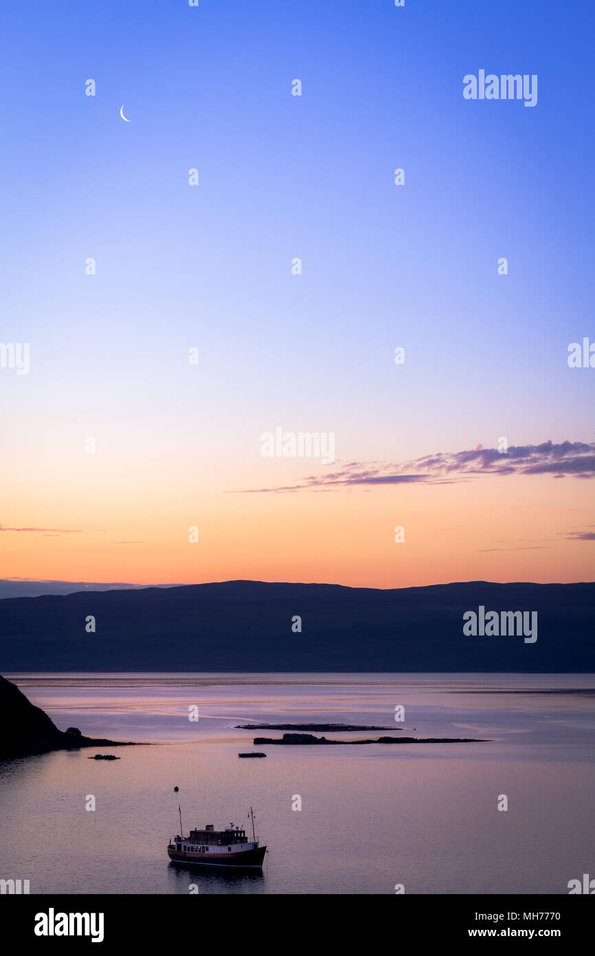 Boat on the water during dusk just before sunrise with the moon and blue and orange color - Stock Image