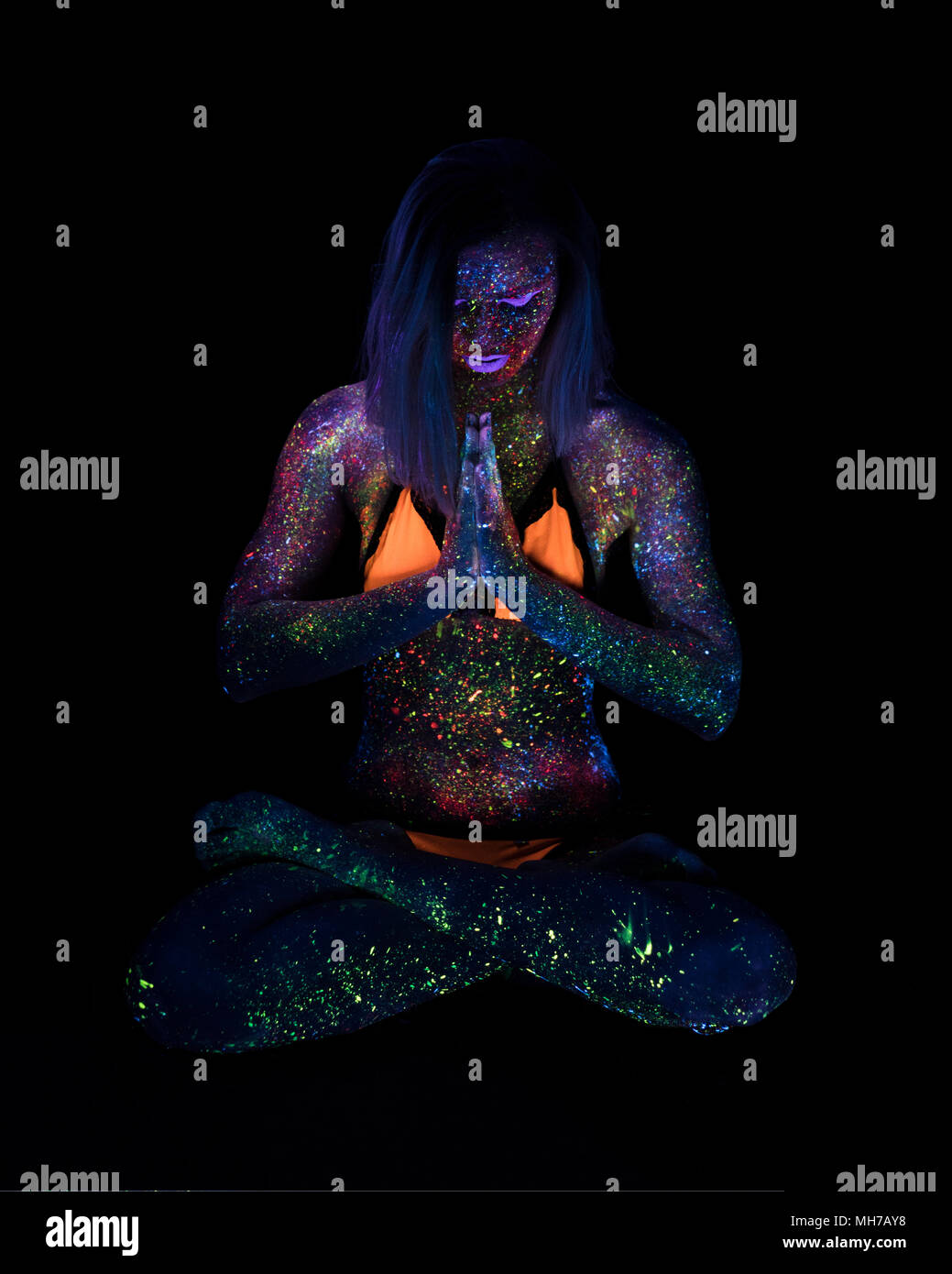 Portrait of Beautiful Fashion Woman Doing Yoga in Neon UF Light. Model Girl with Fluorescent Creative Psychedelic MakeUp, Art Design of Female Disco Dancer Model in UV - Stock Image