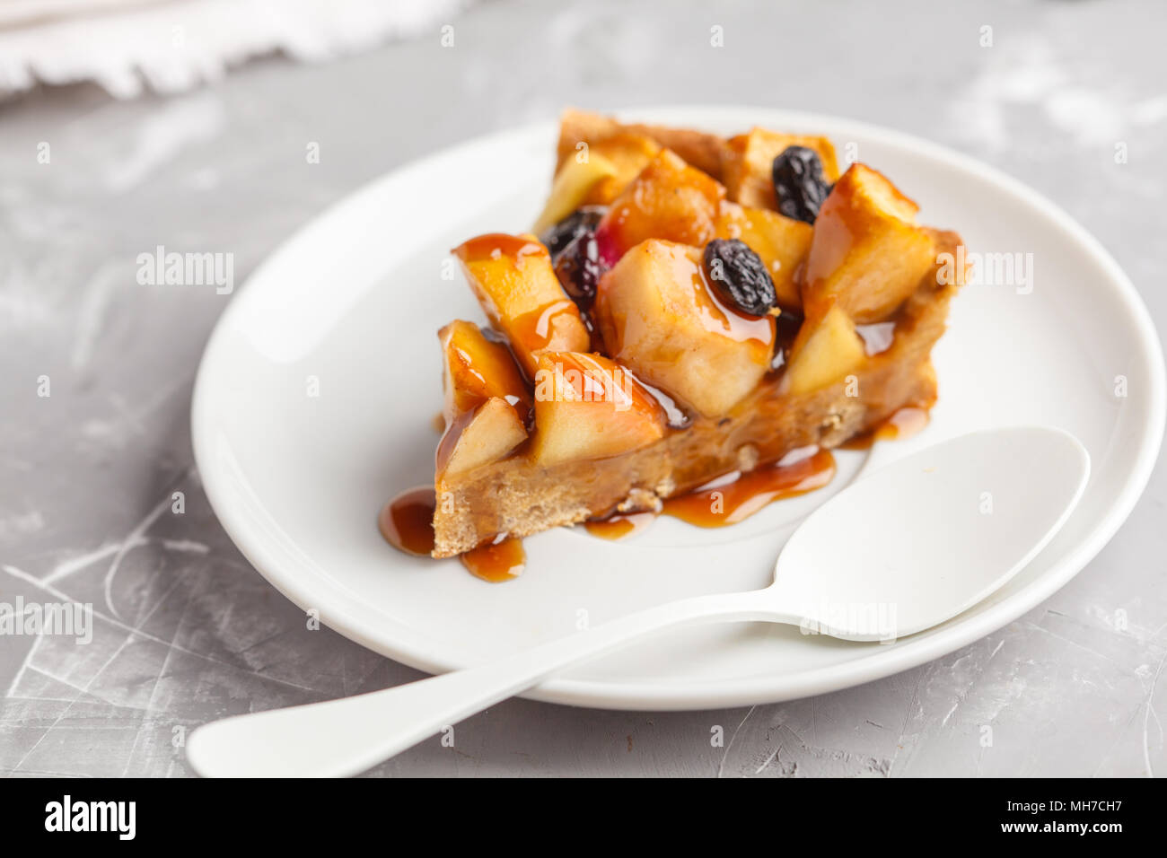 Piece of vegan apple pie with cinnamon, raisins and caramel, gray background. - Stock Image
