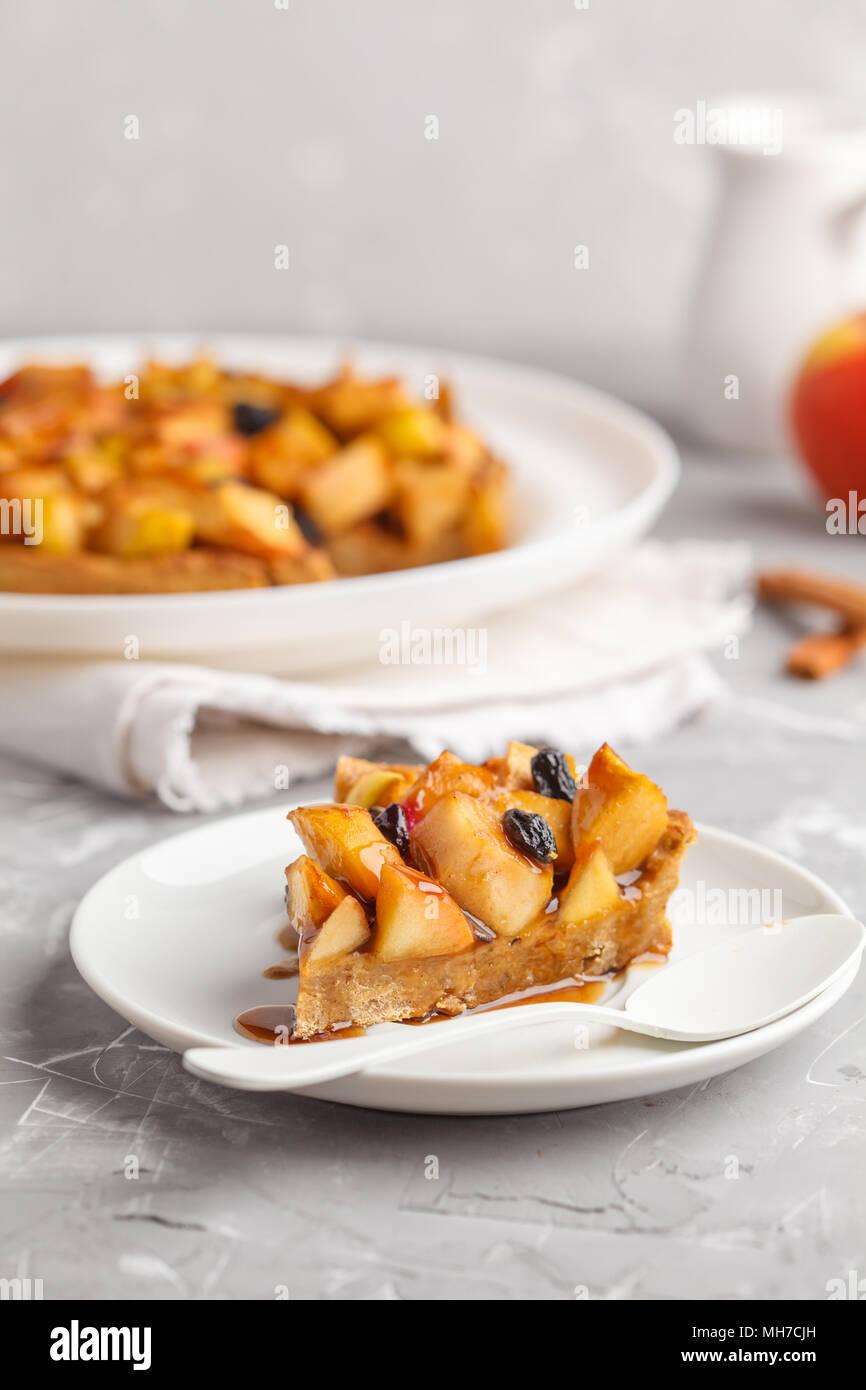 Piece of vegan apple pie with cinnamon, raisins and caramel, gray background. - Stock Image