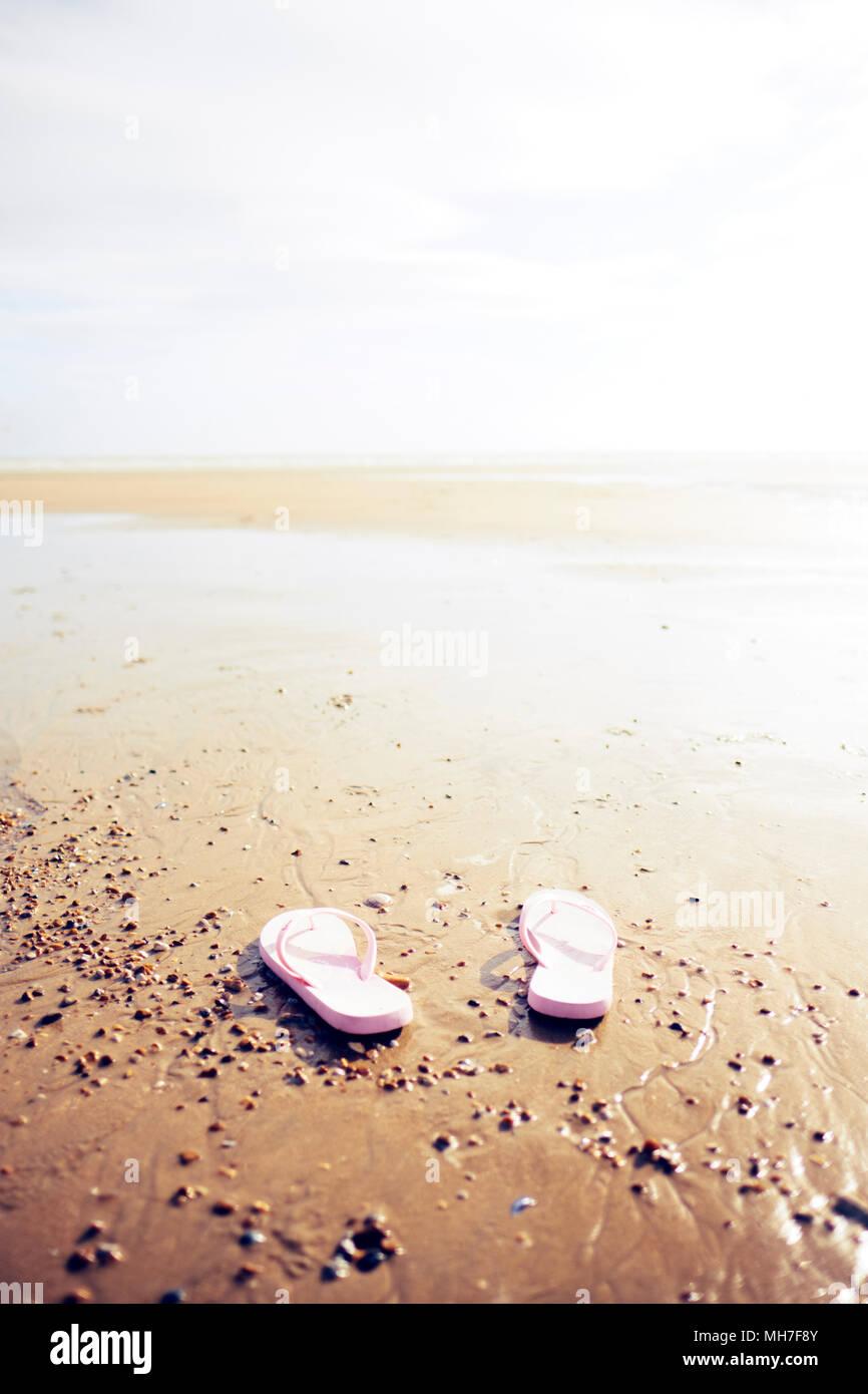 A pair of pink flip flops on a sandy summer beach  (minimal focus) - Stock Image