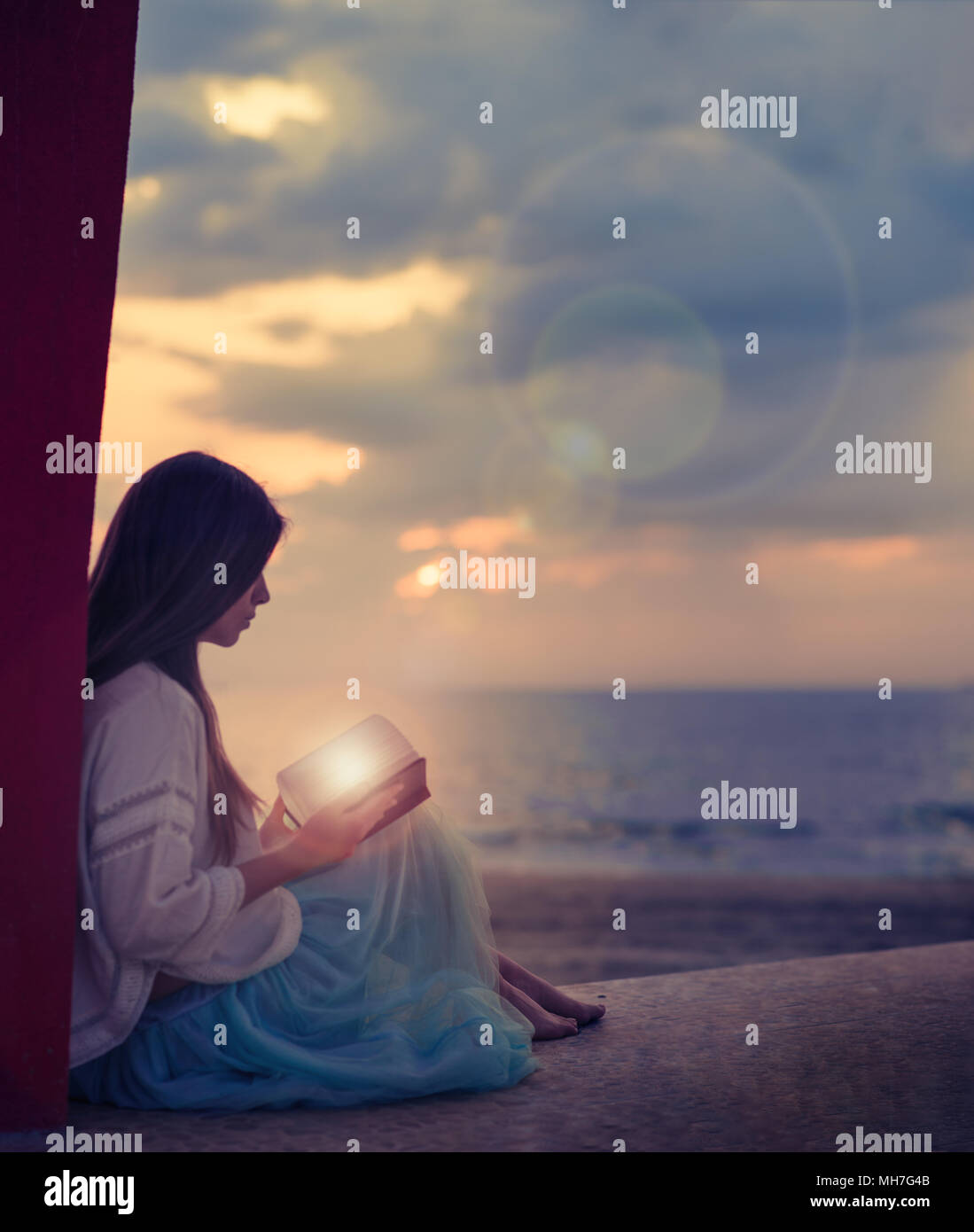 girl reading a magic book sitting at sea shore - Stock Image
