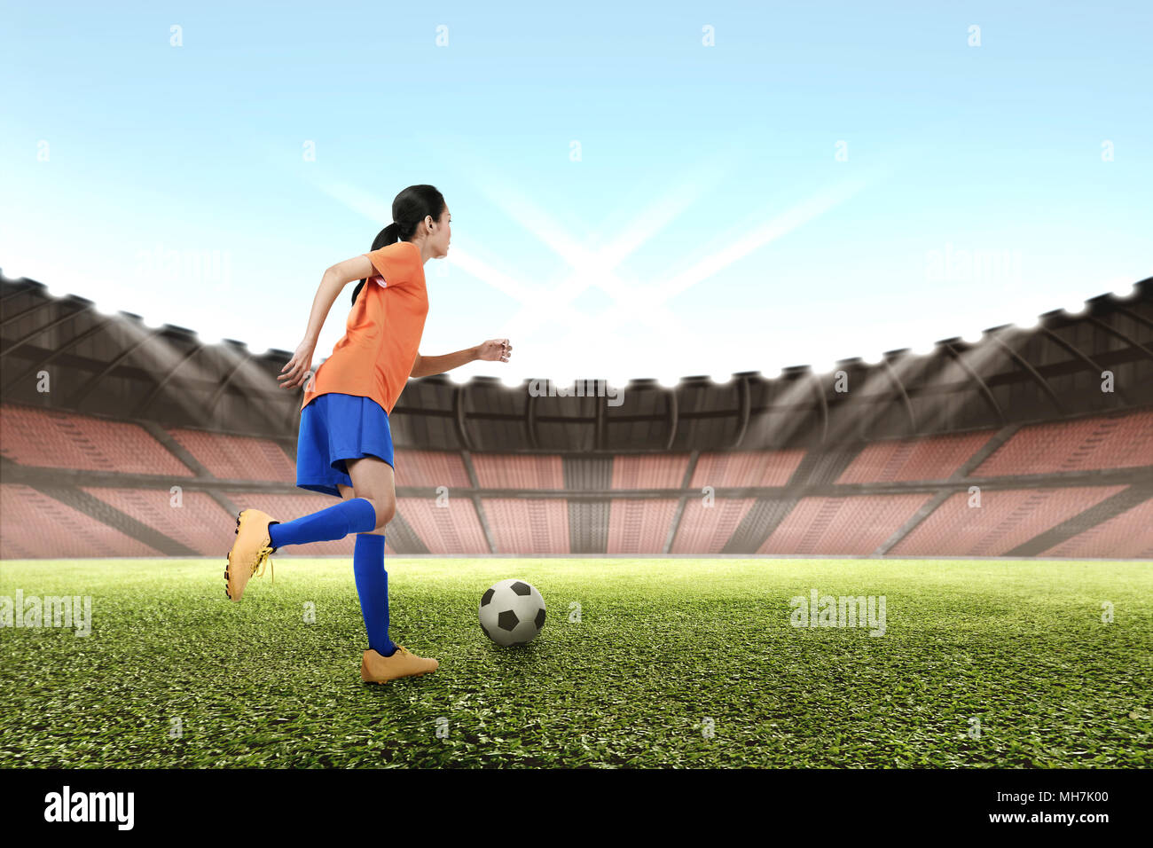 Image of asian female footballer kicking the ball on the field - Stock Image
