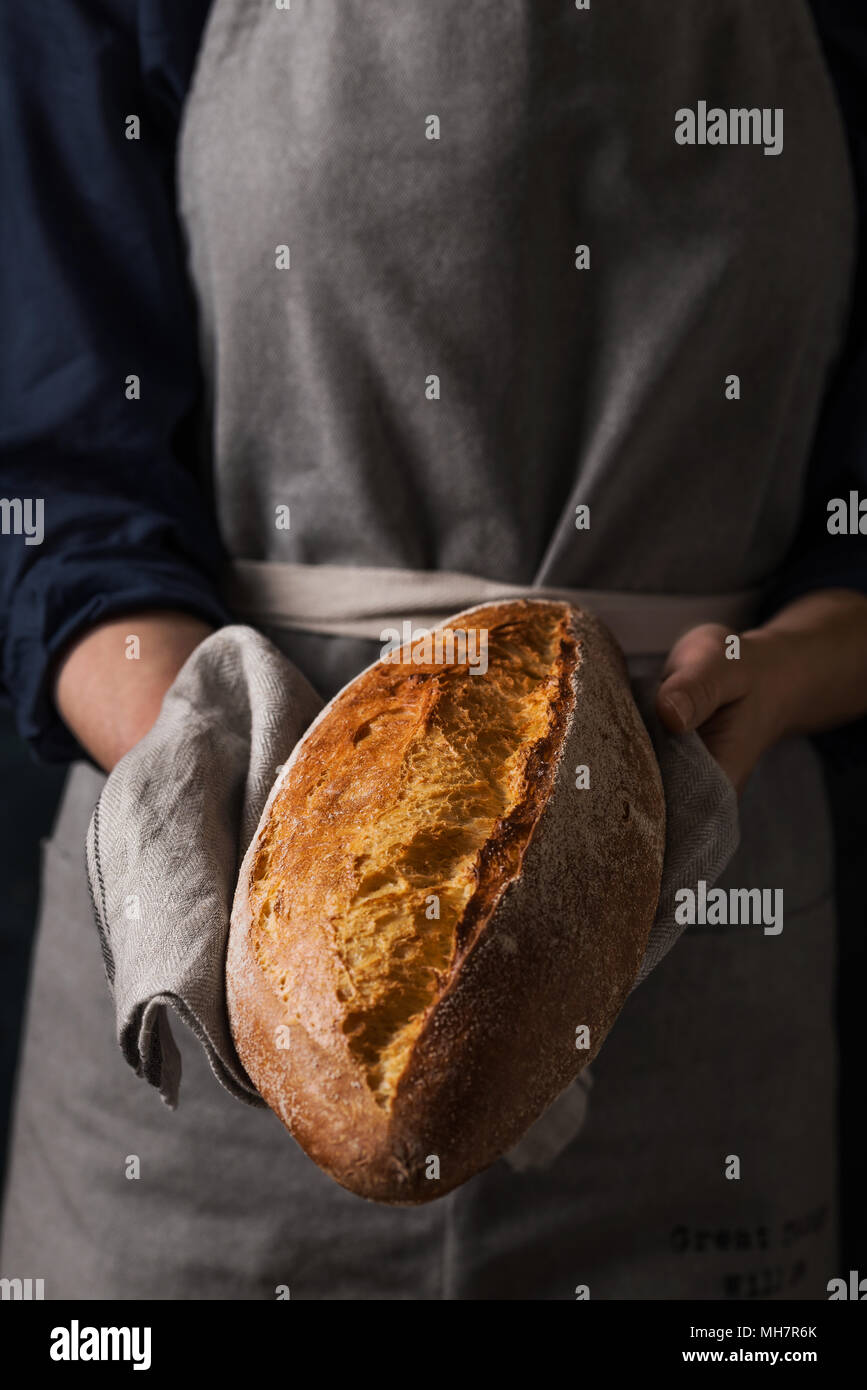 Baker holding fresh homemade bread. Composition in dark colors Stock Photo