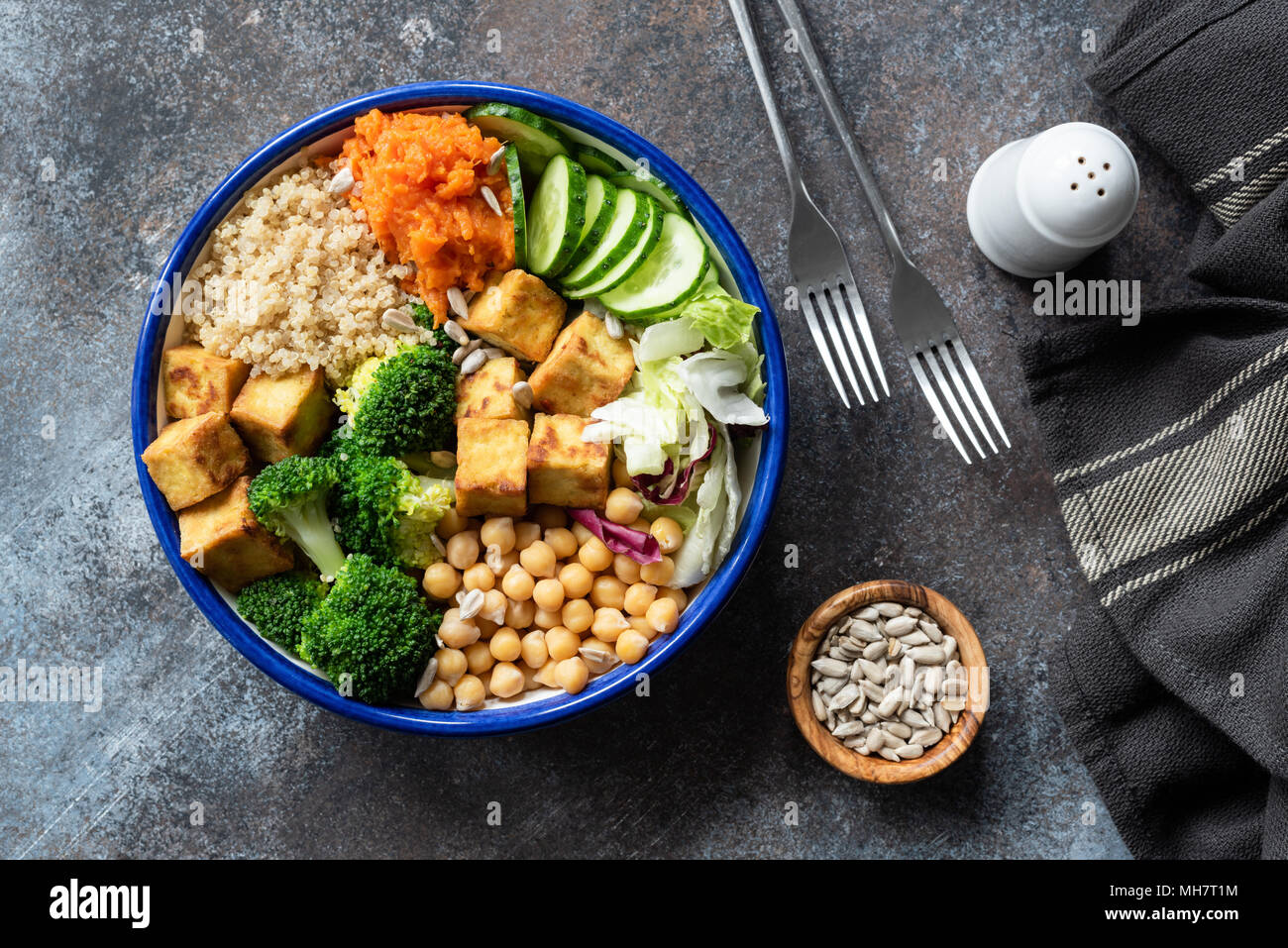 Colorful Buddha bowl on dark background, top view. Buddha bowl with quinoa, tofu, broccoli, sweet potato, chickpea and cucumber. Healthy vegetarian sa - Stock Image