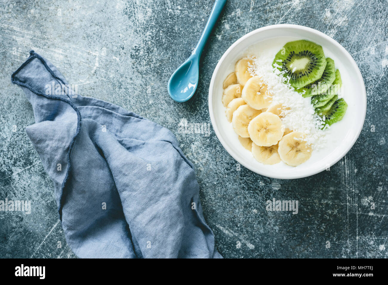 Yogurt with banana, kiwi and coconut bowl. Vegan yogurt with fruits. Healthy eating, dieting, fitness, healthy lifestyle concept. Table top view - Stock Image