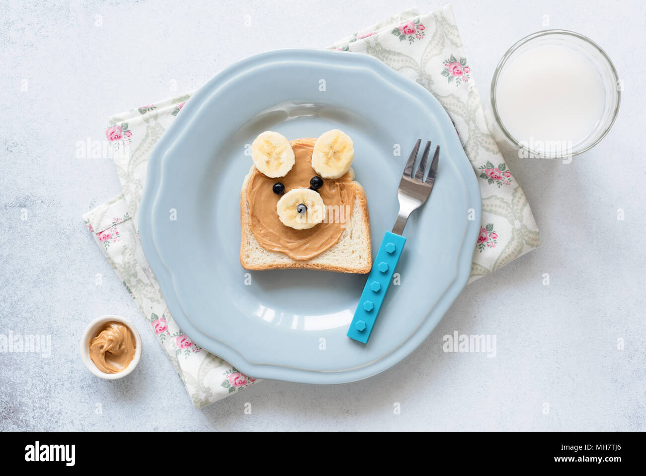 Banana peanut butter toast on a blue plate, meal for kids. Cute funny bear shaped animal toast with nut butter and banana. School lunch for kids. Heal - Stock Image