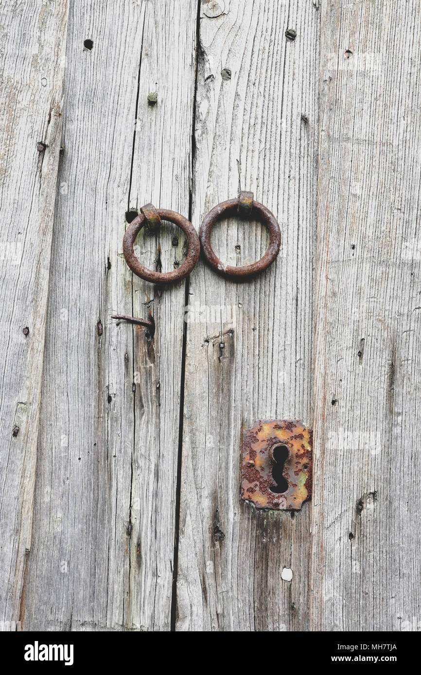 Old wooden doors with bronze handles and keyhole. - Stock Image