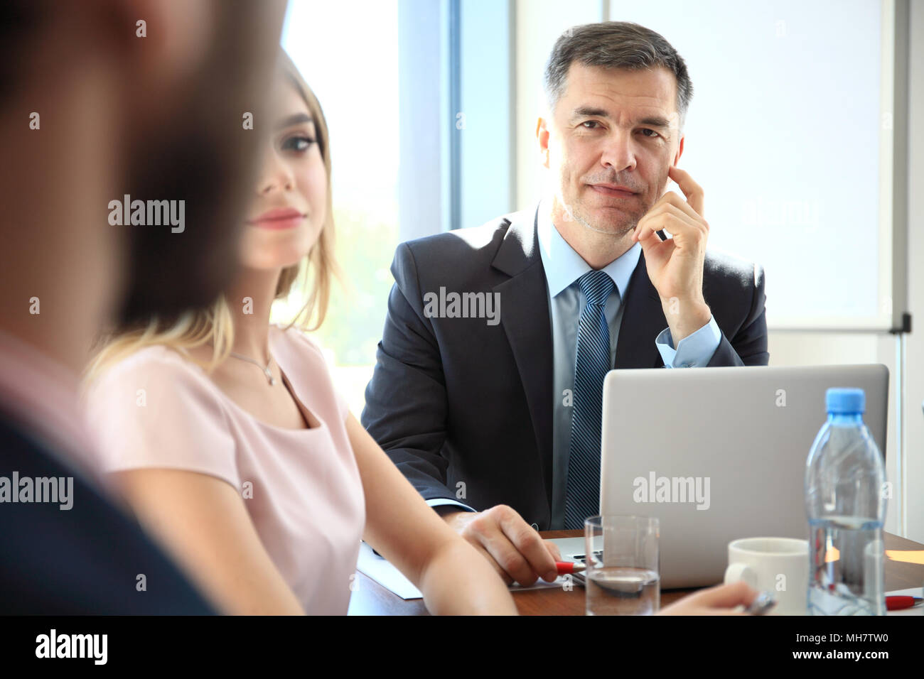 Portrait of a handsome businessman, blurred colleagues in the background. - Stock Image