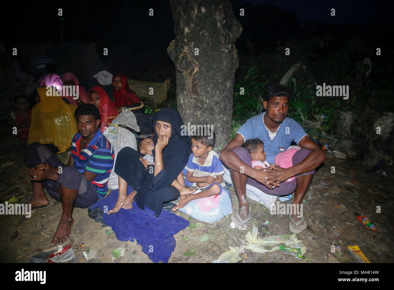 Rohingya refugees take shelter under open sky beside a road at Teknaf after entering Bangladesh through border point at Ukhia in Cox's Bazar, Banglad - Stock Image