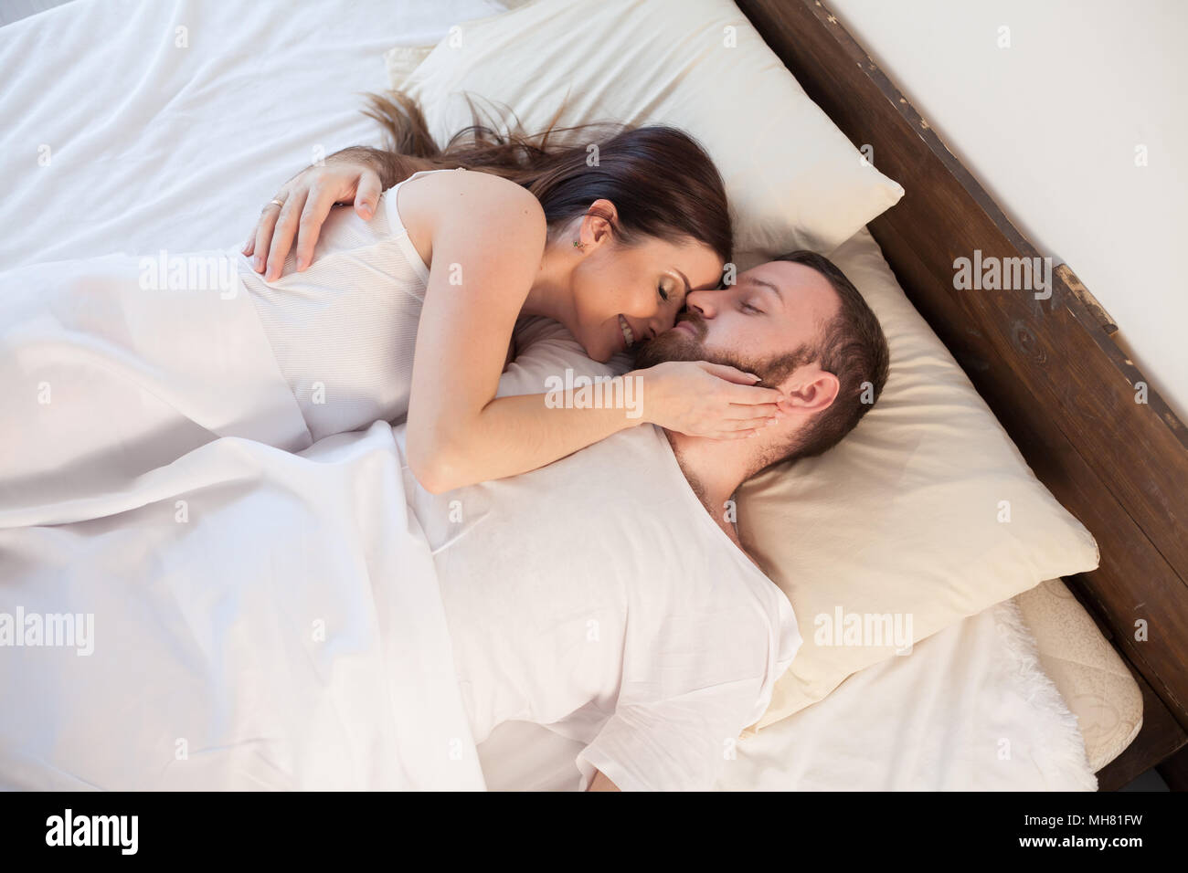 Husband And Wife Are Sleeping In Beds With White Linen Stock Photo