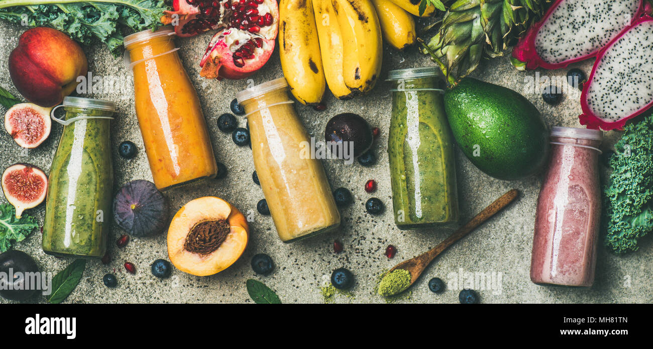 Colorful smoothies in bottles with fresh fruit, copy space Stock Photo