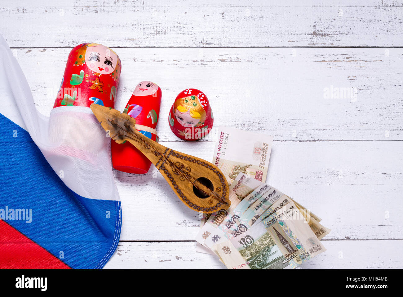 Russian symbols matryoshka, balalaika, rubles cash and flag of russian federation on wooden background. - Stock Image
