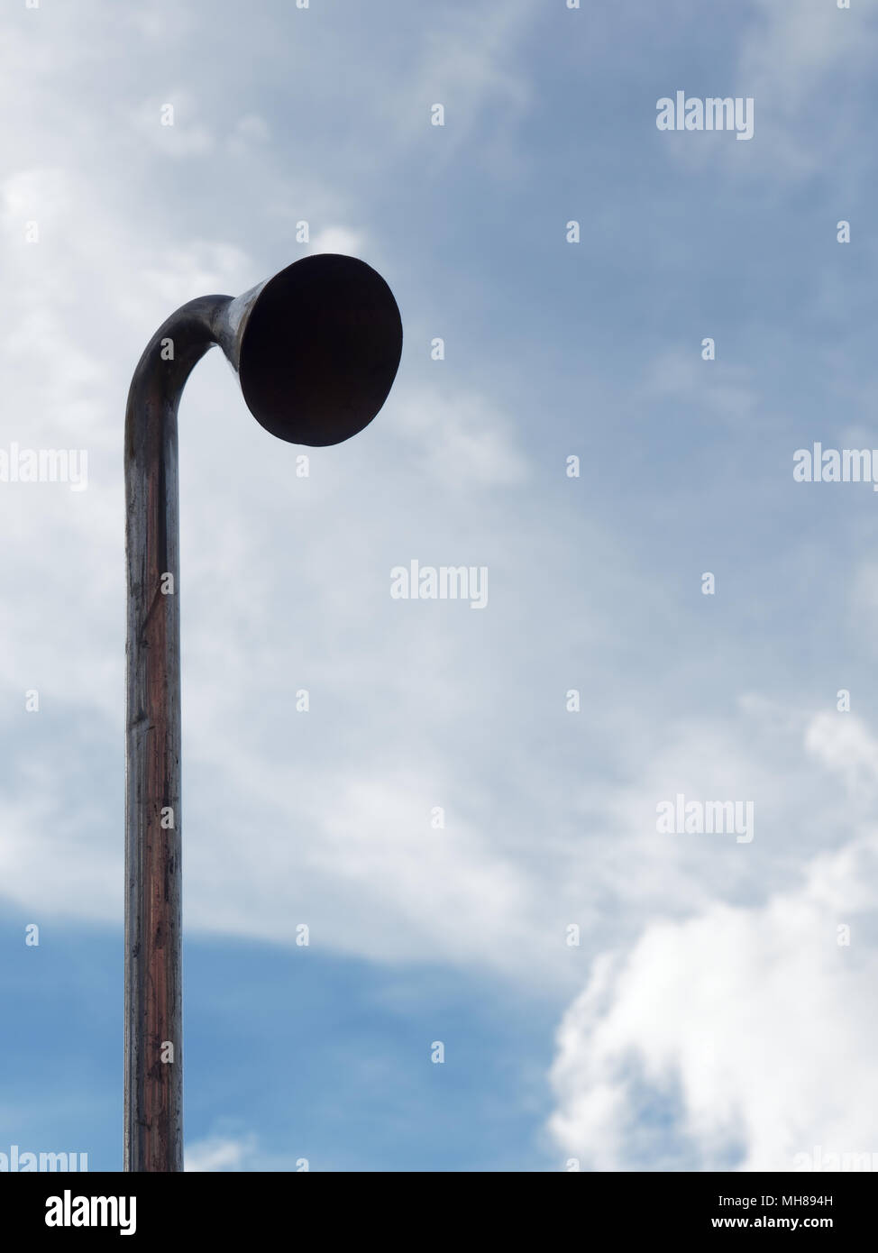 Induction or suction pipe with head for testing air and noise pollution over bright blue sky background sucking cloud into tube with concepts of business, environment, suction, industry and pollution - Stock Image