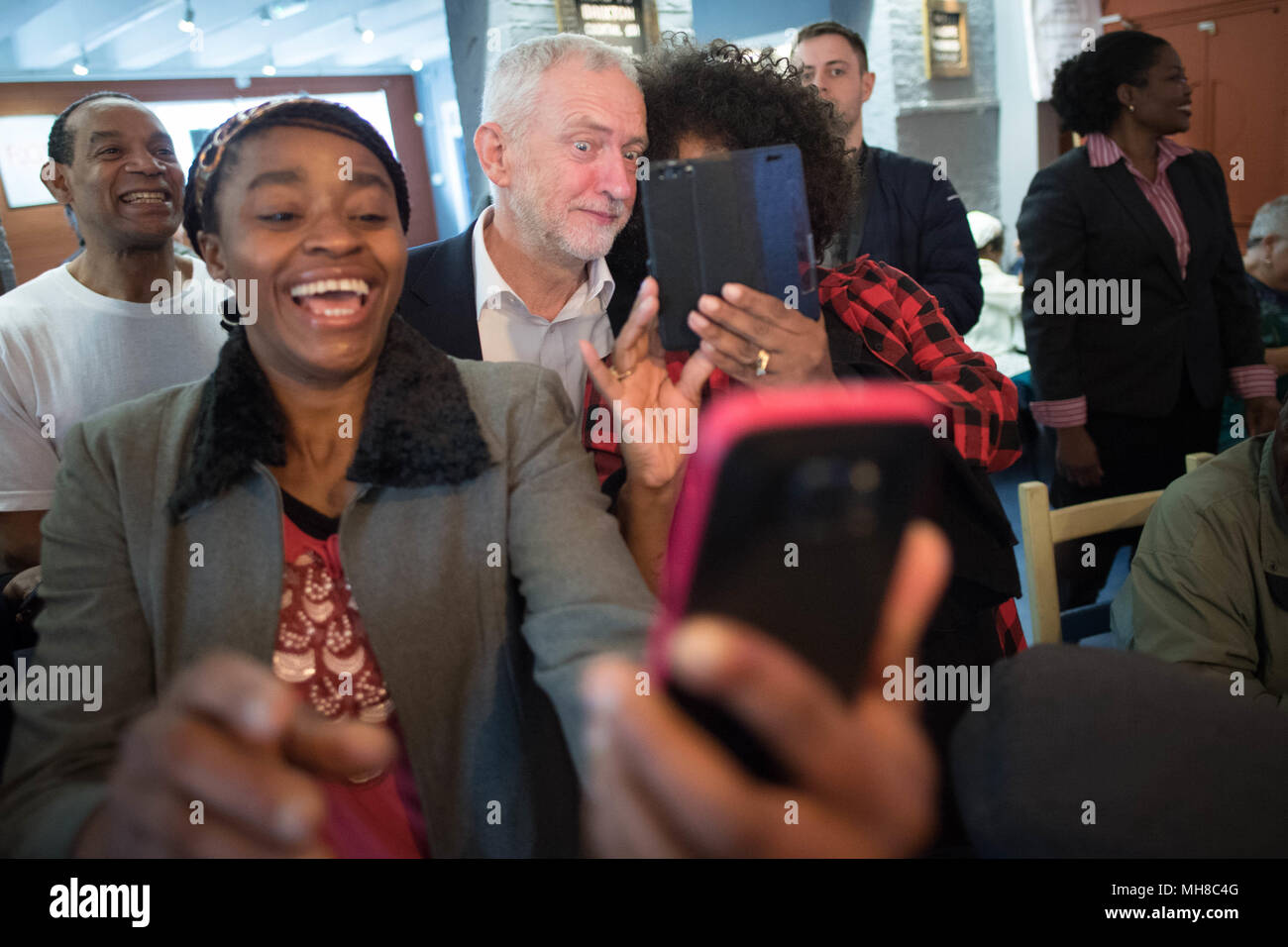 Labour leader Jeremy Corbyn poses for selfies as he meets people from the Caribbean and the West Indies, members of the Stockwell Good Neighbours community group, at the Oval House Theatre in Kennington, south London. - Stock Image