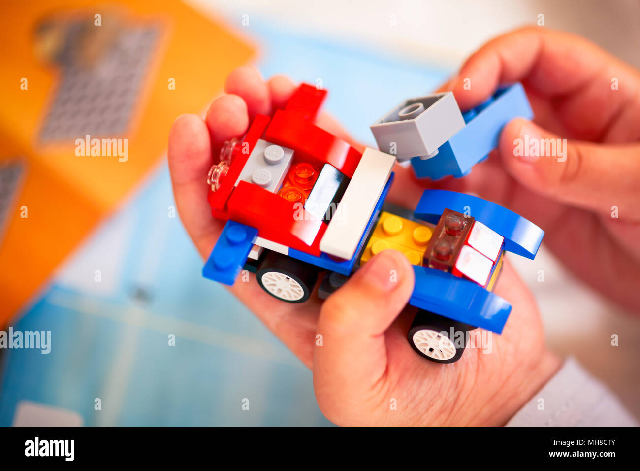 Tambov, Russian Federation - December 19, 2013 Child building Lego car. There are  Lego instructions in background. - Stock Image