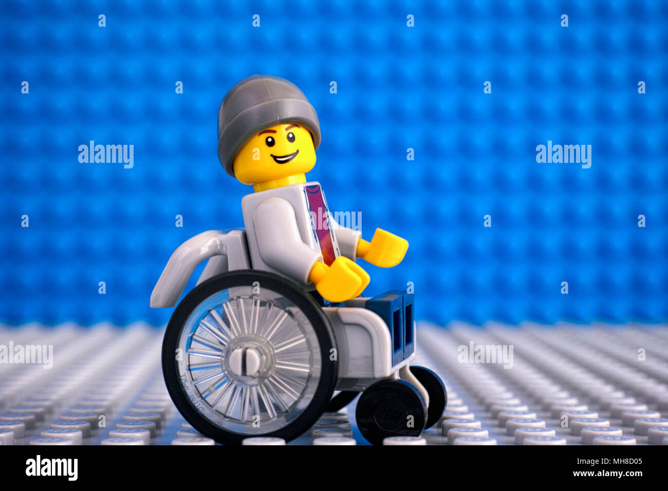 Tambov, Russian Federation - February 05, 2018 Lego boy minifigure in wheelchair. Blue and gray baseplates background. Studio shot. - Stock Image