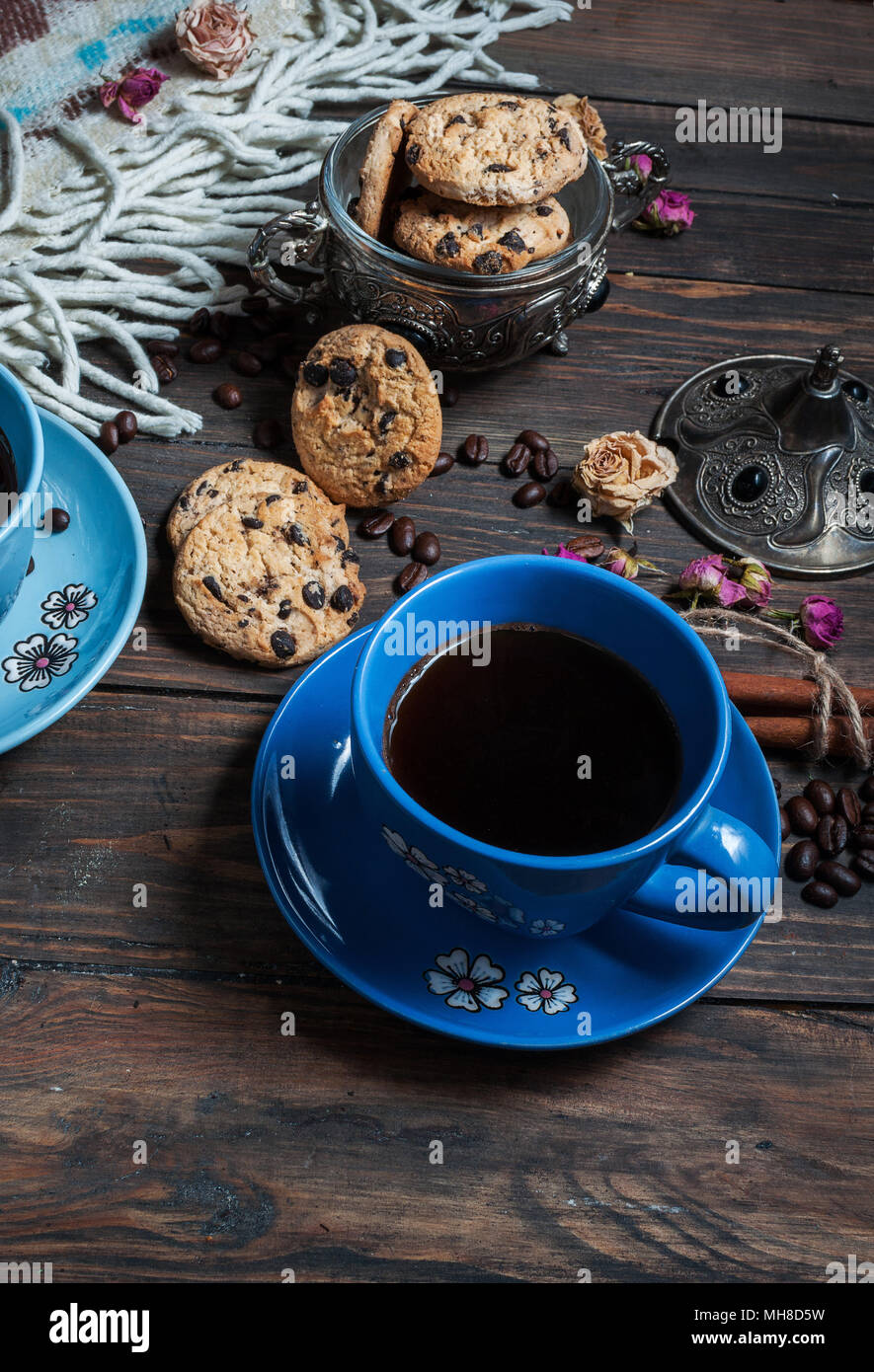 The cup of coffee, coffee beans and cookies-hearts related together on  wooden table. Stock Photo
