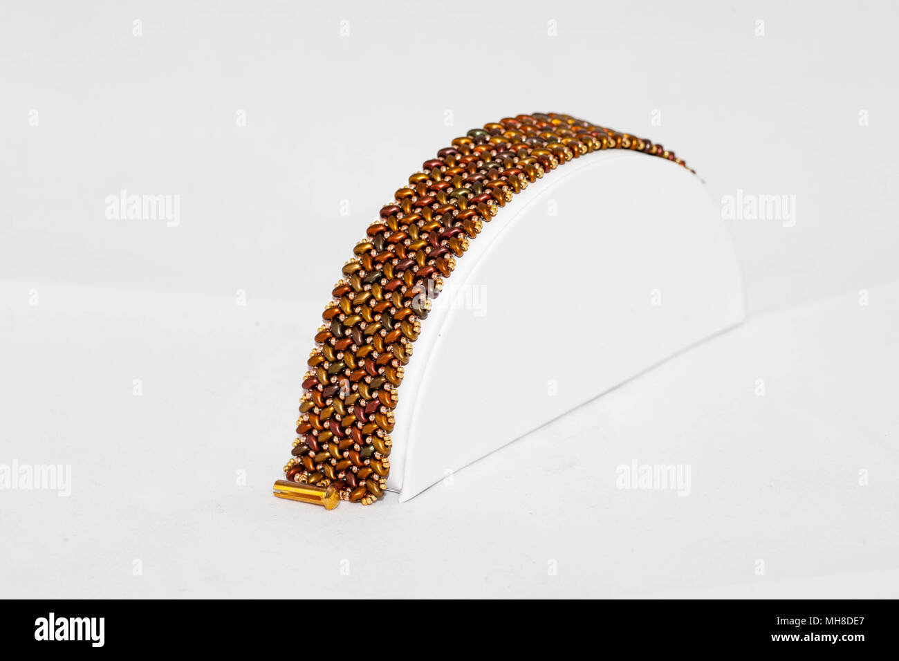 a brown and gold hand stitched flat beaded bracelet - Stock Image